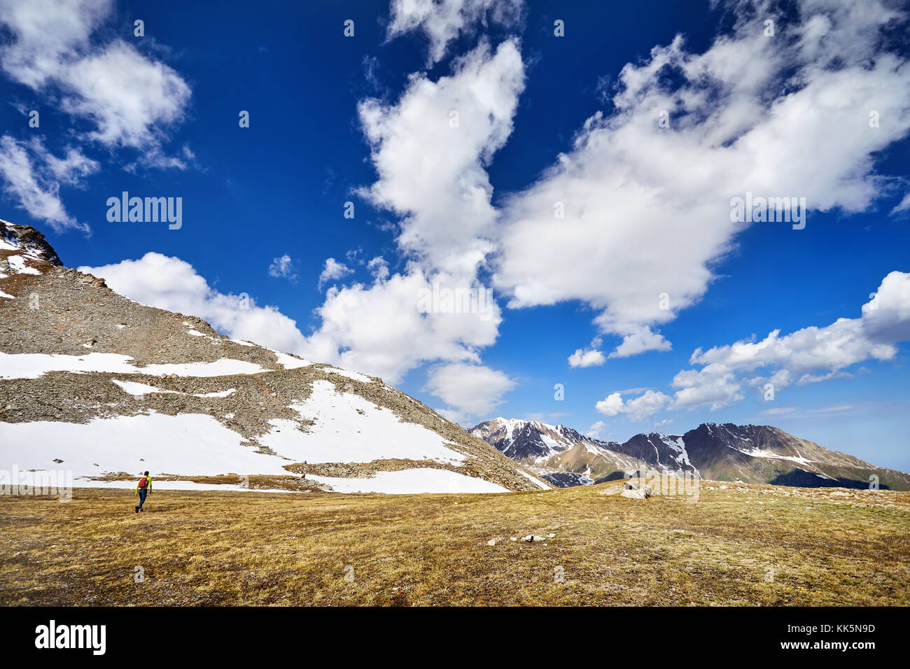 Hiker in yellow shirt with backpack walking in the snowy mountains at cloudy sky background - Stock Image