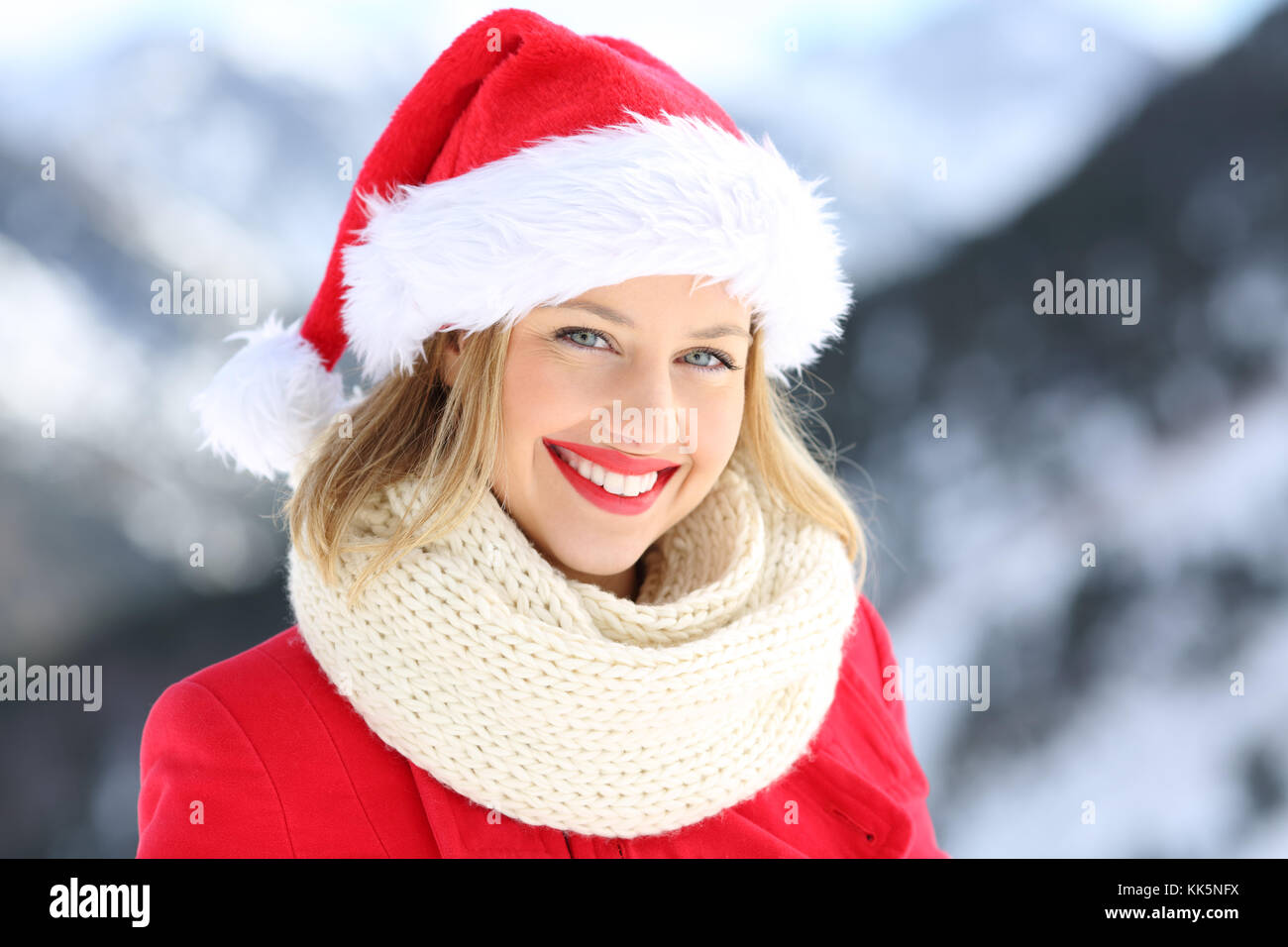 cdb5ed9d26ba4 Portrait of a happy woman posing with santa claus hat in christmas holidays  with a snowy mountain in the background