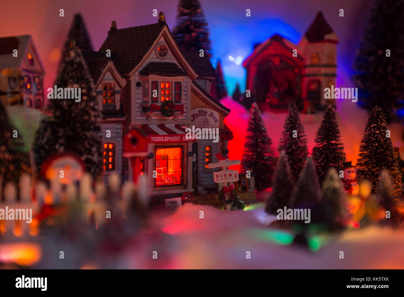 Christmas background of snow miniature village with store front reads jolly joy arts and crafts - Stock Image