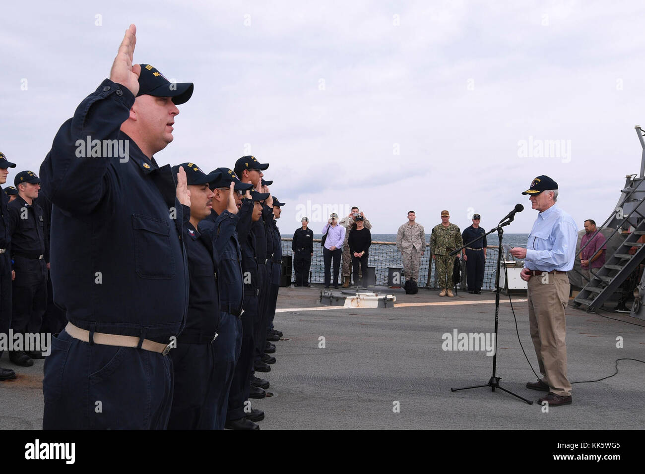 ARABIAN GULF (Nov. 23, 2017) Secretary of the Navy Richard V. Spencer reenlists eight Sailors assigned to the Arleigh - Stock Image