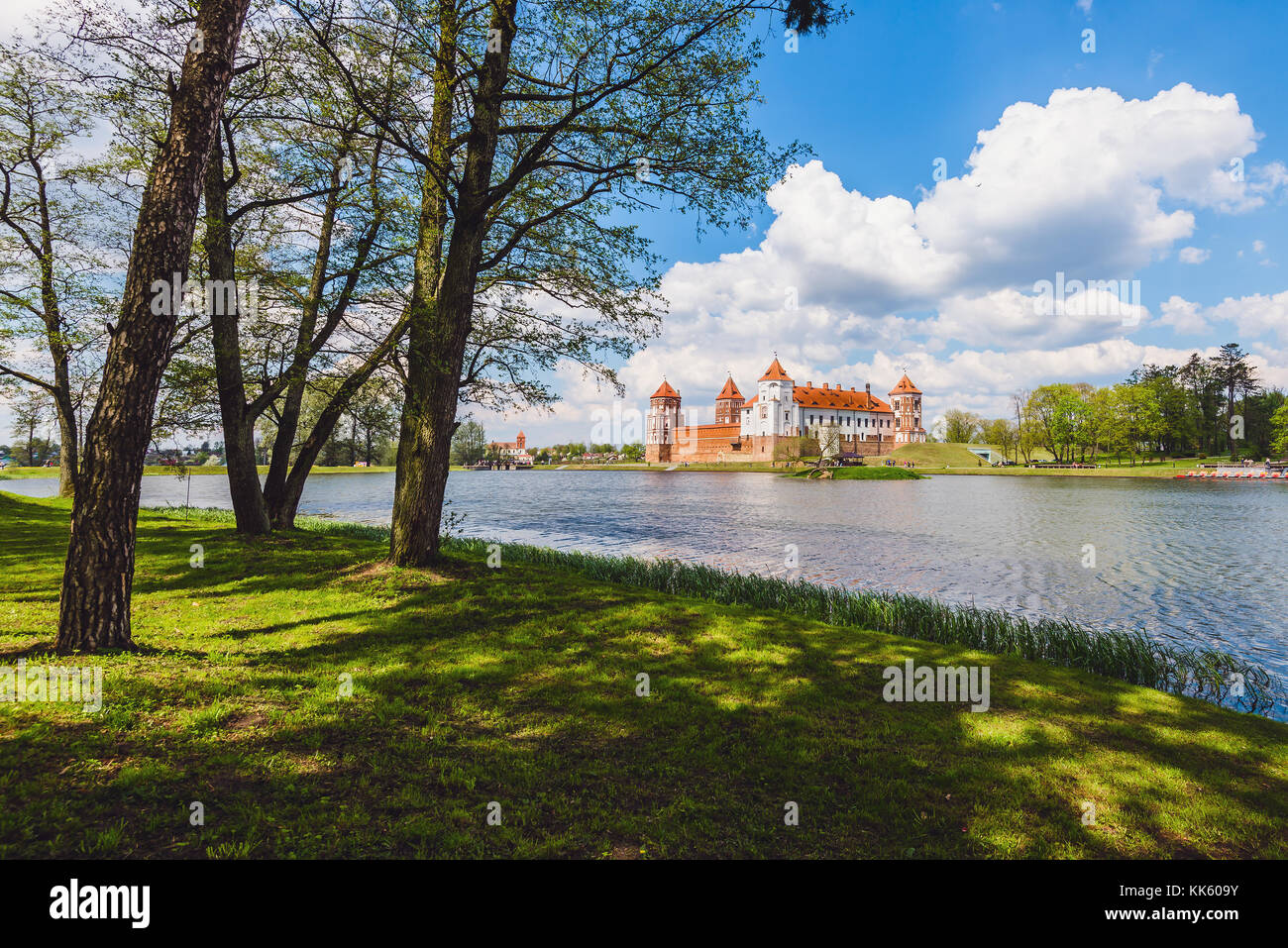 Medieval Mir Castle Complex in Belarus. Ancient brick Mirsky castle and clouds reflected on blue water. Unesco world - Stock Image