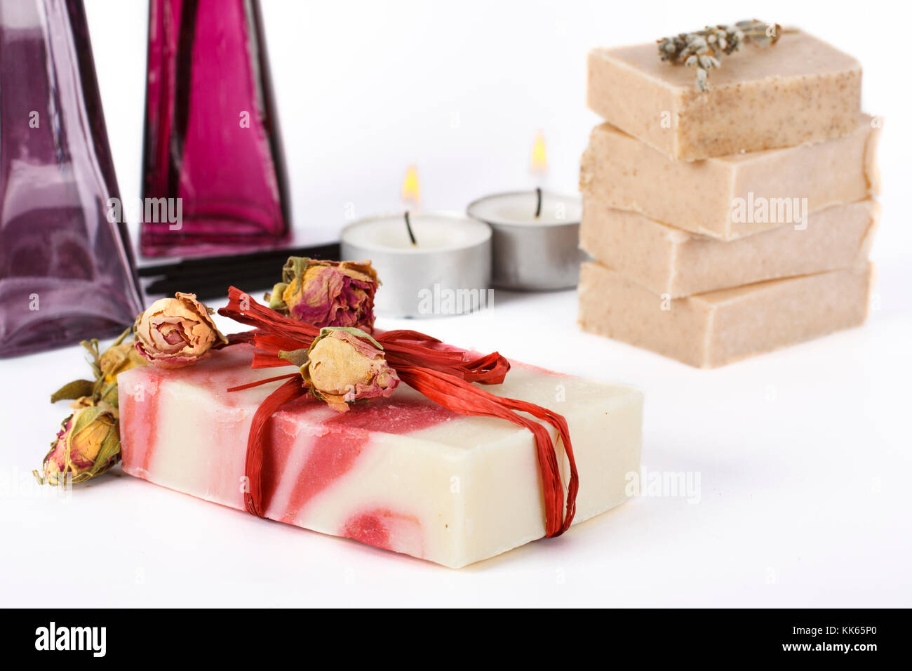 Handmade soap surrounded by natural ingredients and candle and soaps at background. - Stock Image