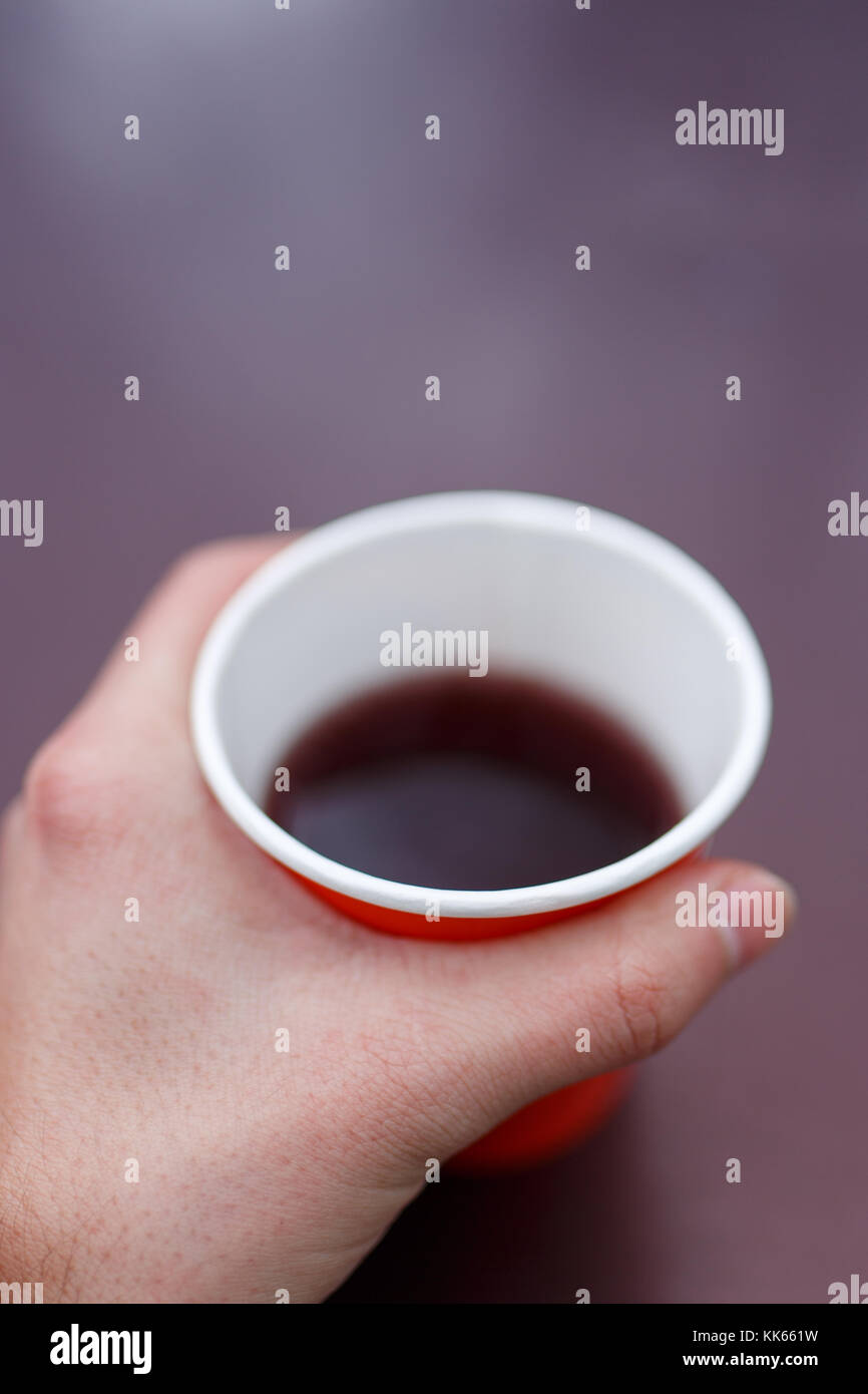 Image of man's hand holding red paper glass with tea on blurred violet background - Stock Image