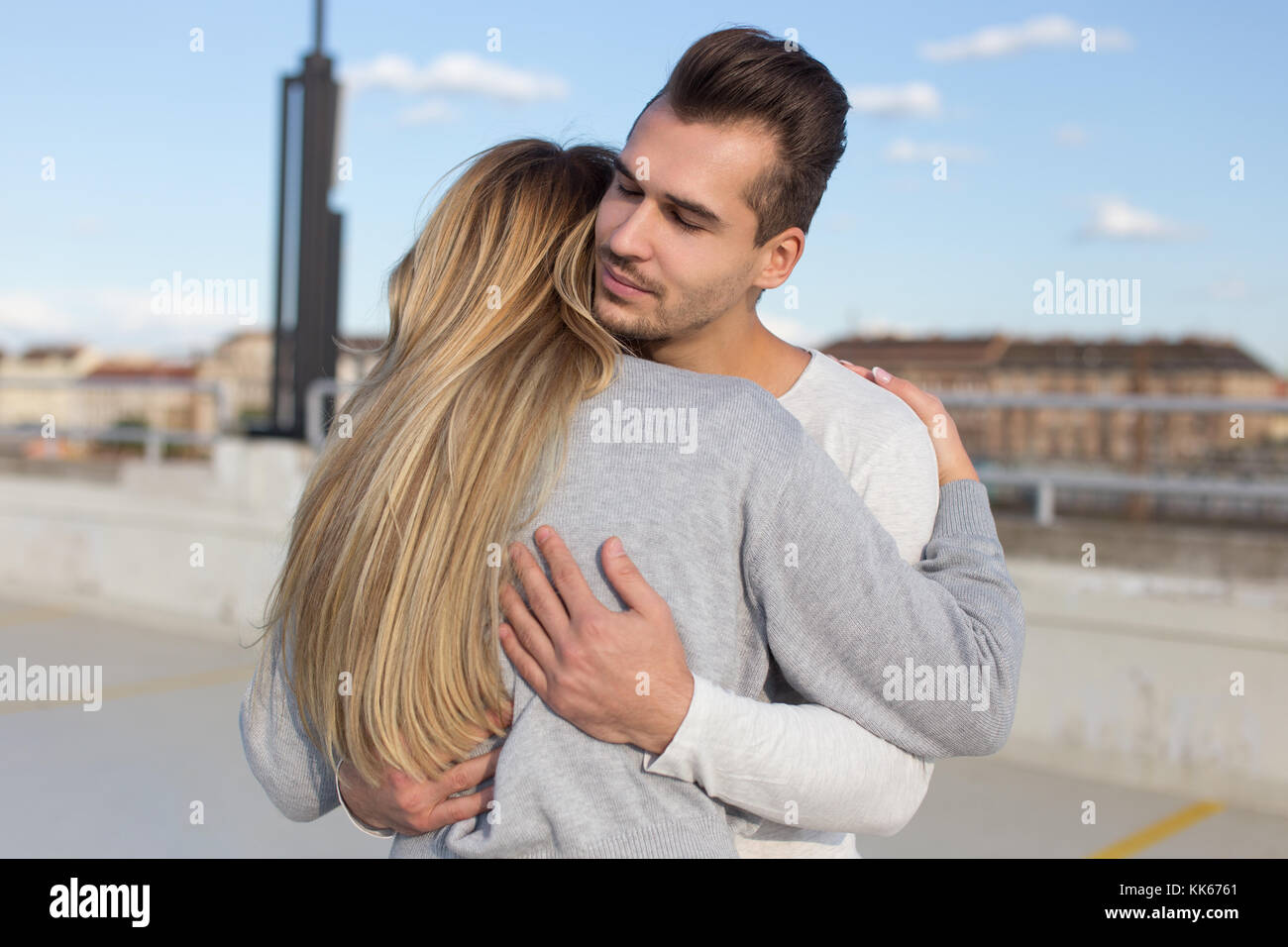 Young man cuddle girlfriend outdoors, understanding and love - Stock Image
