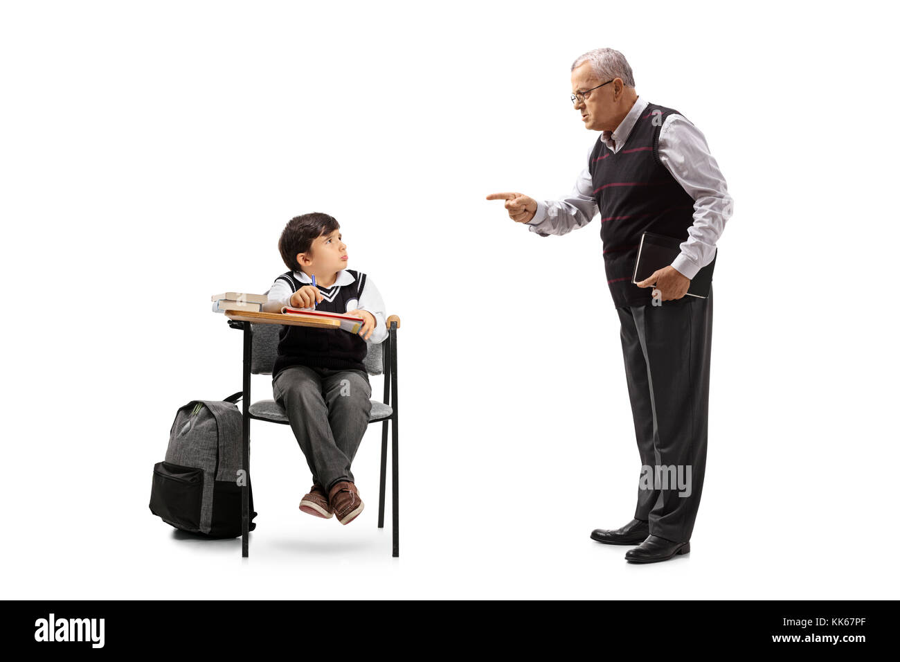 Teacher scolding a little schoolboy seated in a school chair isolated on white background - Stock Image