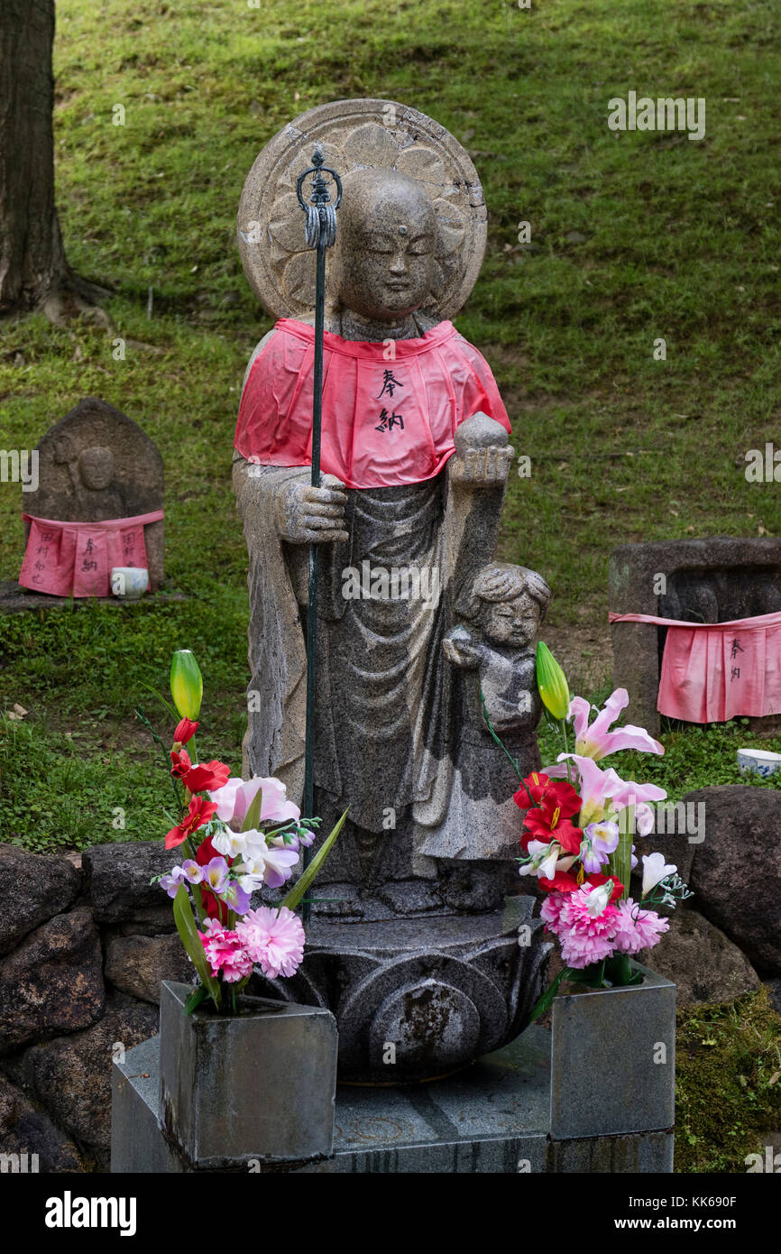 Nara - Japan, May 30, 2017: Traditional stone carved Jizo with red skirt honored and respected with flowers Stock Photo