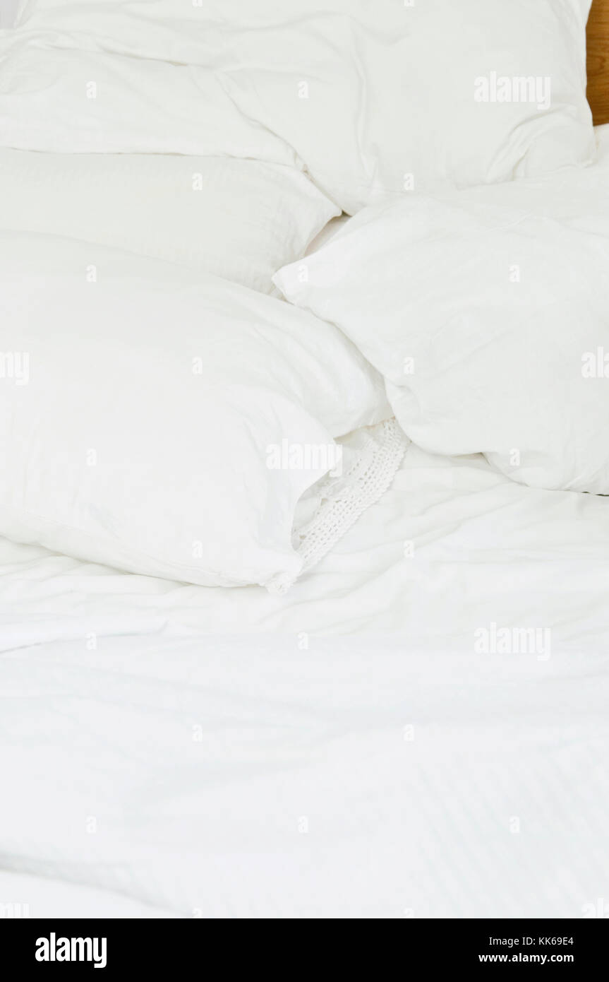 A bed with white sheets. - Stock Image