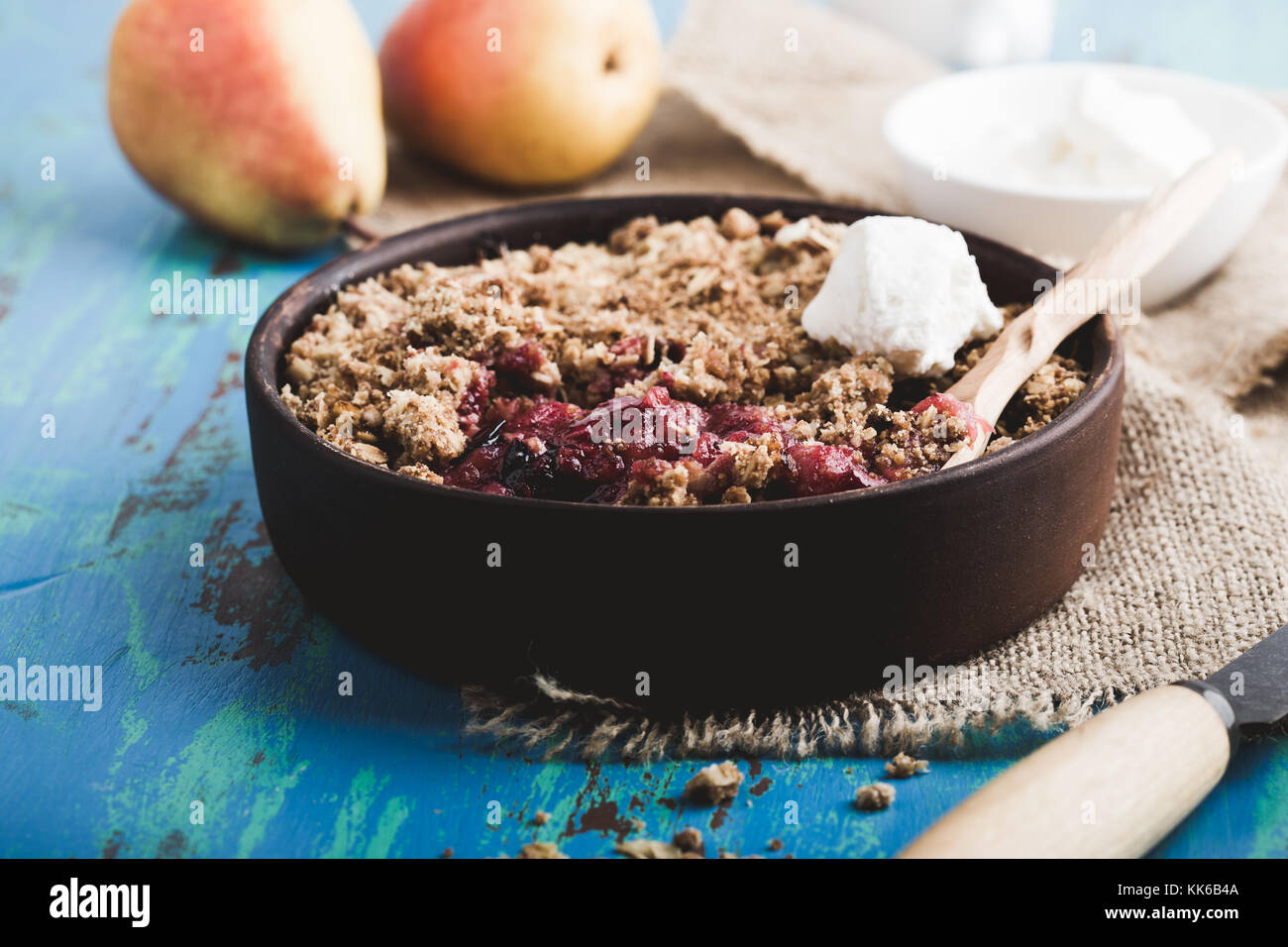 Pear and berry crumbles served with cream in rustic ceramic bowl - Stock Image