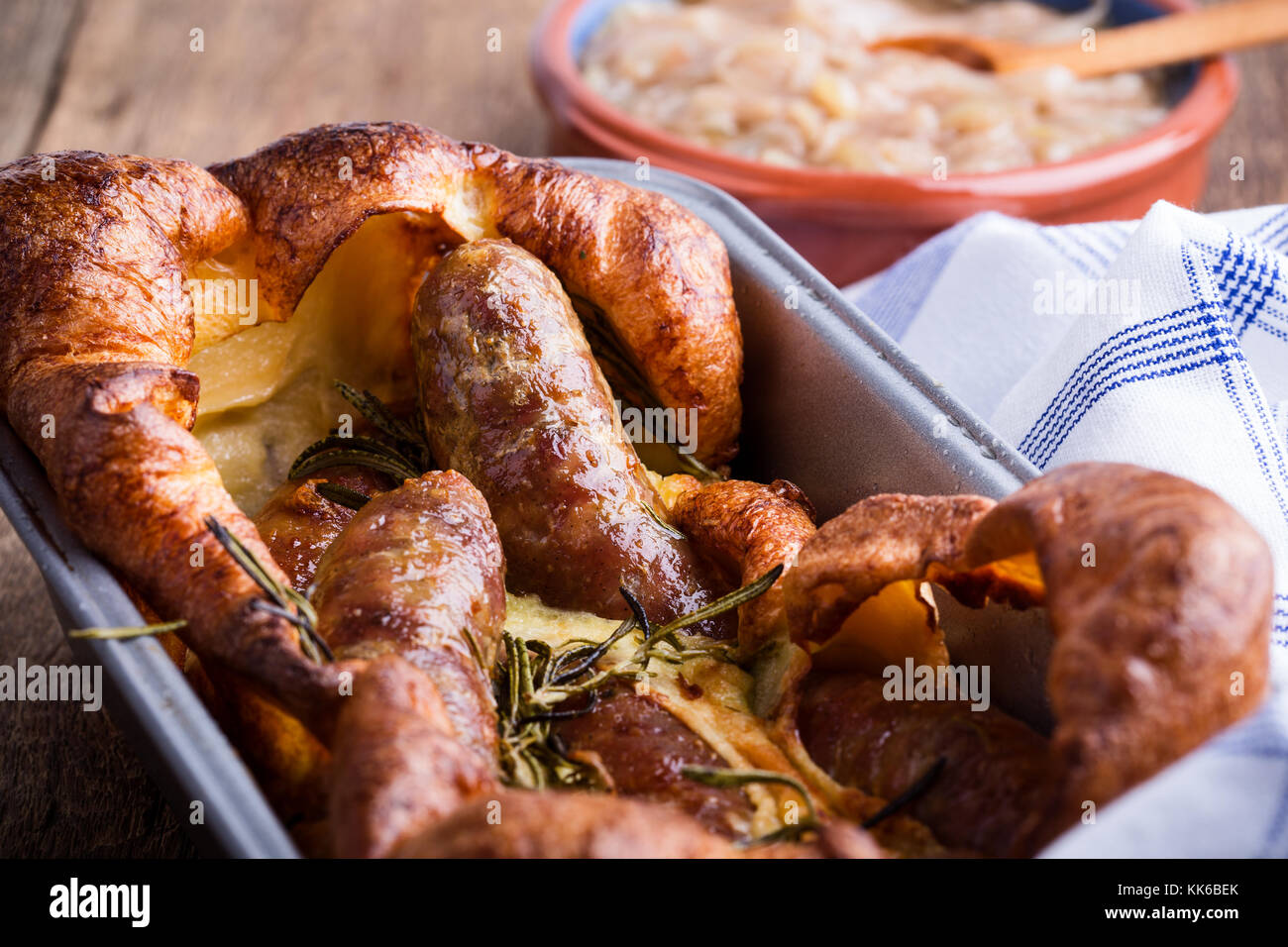 Baked sausages in Yorkshire pudding batter and served with  onion gravy, toad in the hole - Stock Image