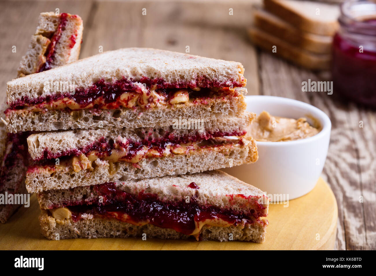 Peanut butter and jelly sandwich with whole wheat bread on rustic wooden table - Stock Image