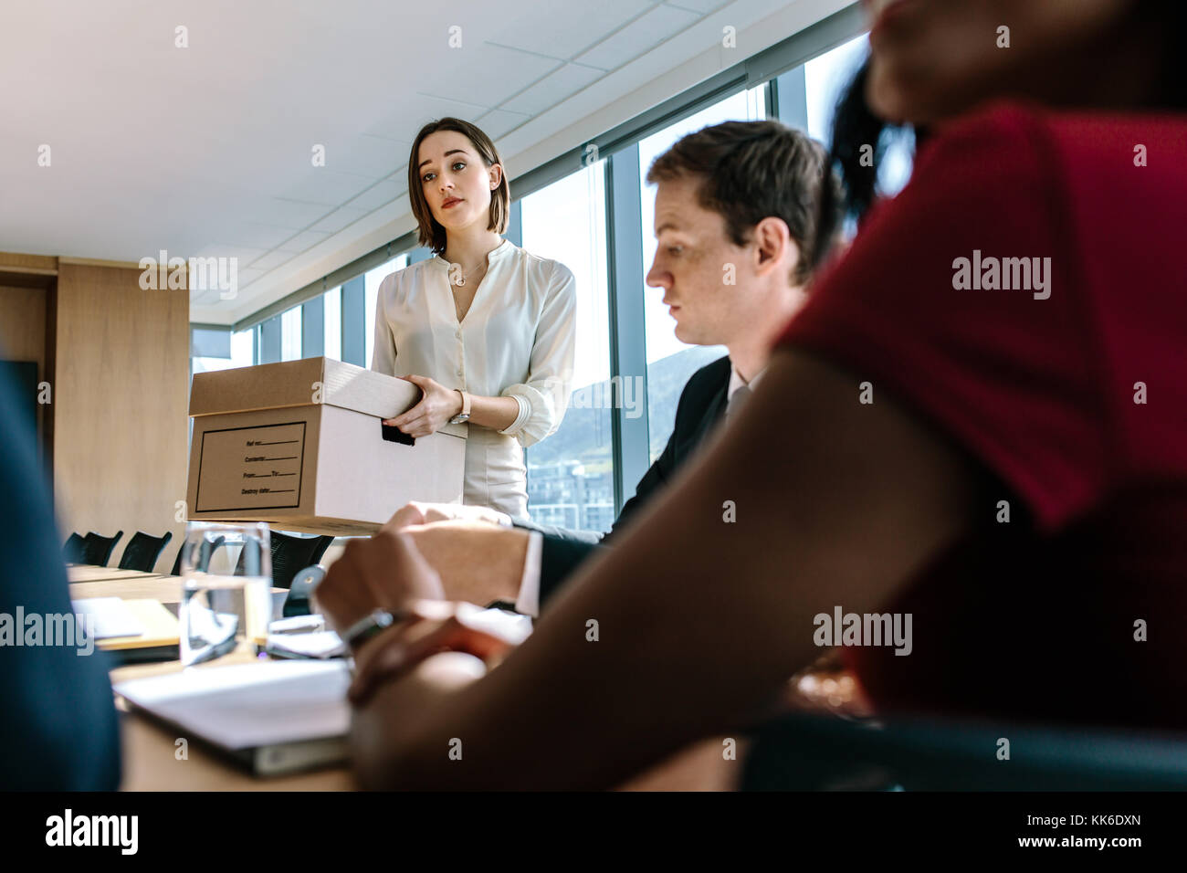 Woman holding a cardboard box at table with colleagues sitting around in conference room. Corporate business people - Stock Image