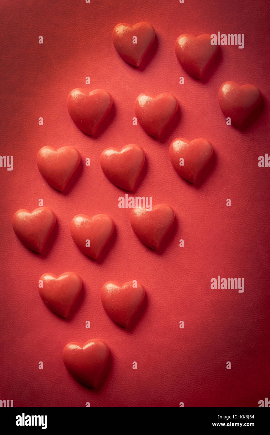red valentines heart shapes on red background - Stock Image