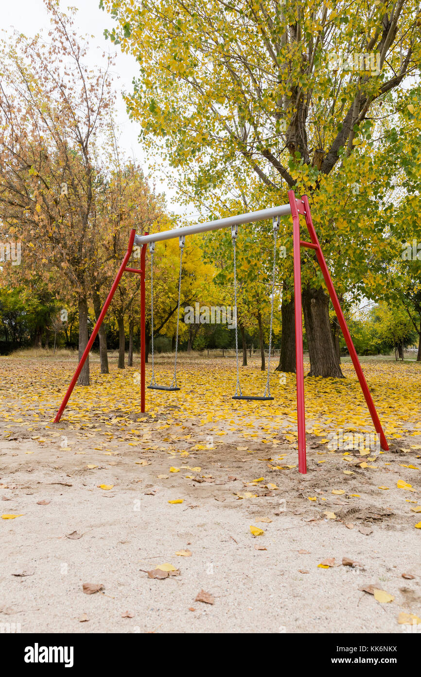 Swings In A Park With Yellow Fallen Leaves Of Trees Stock
