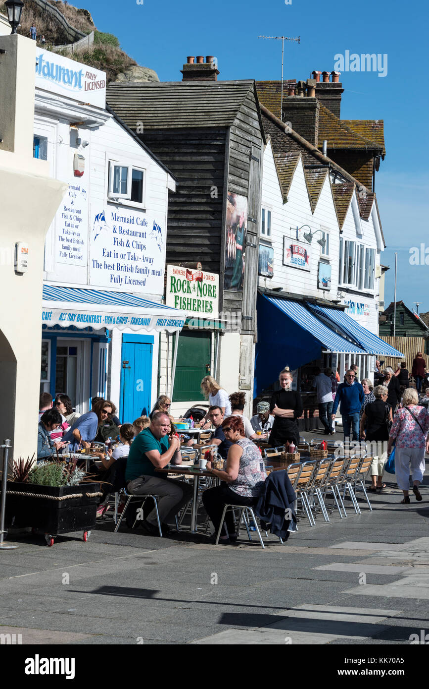 Visitors enjoying a lunch in the autumn sunshine at some  of the cafes and restaurants on the seafront of Hastings - Stock Image