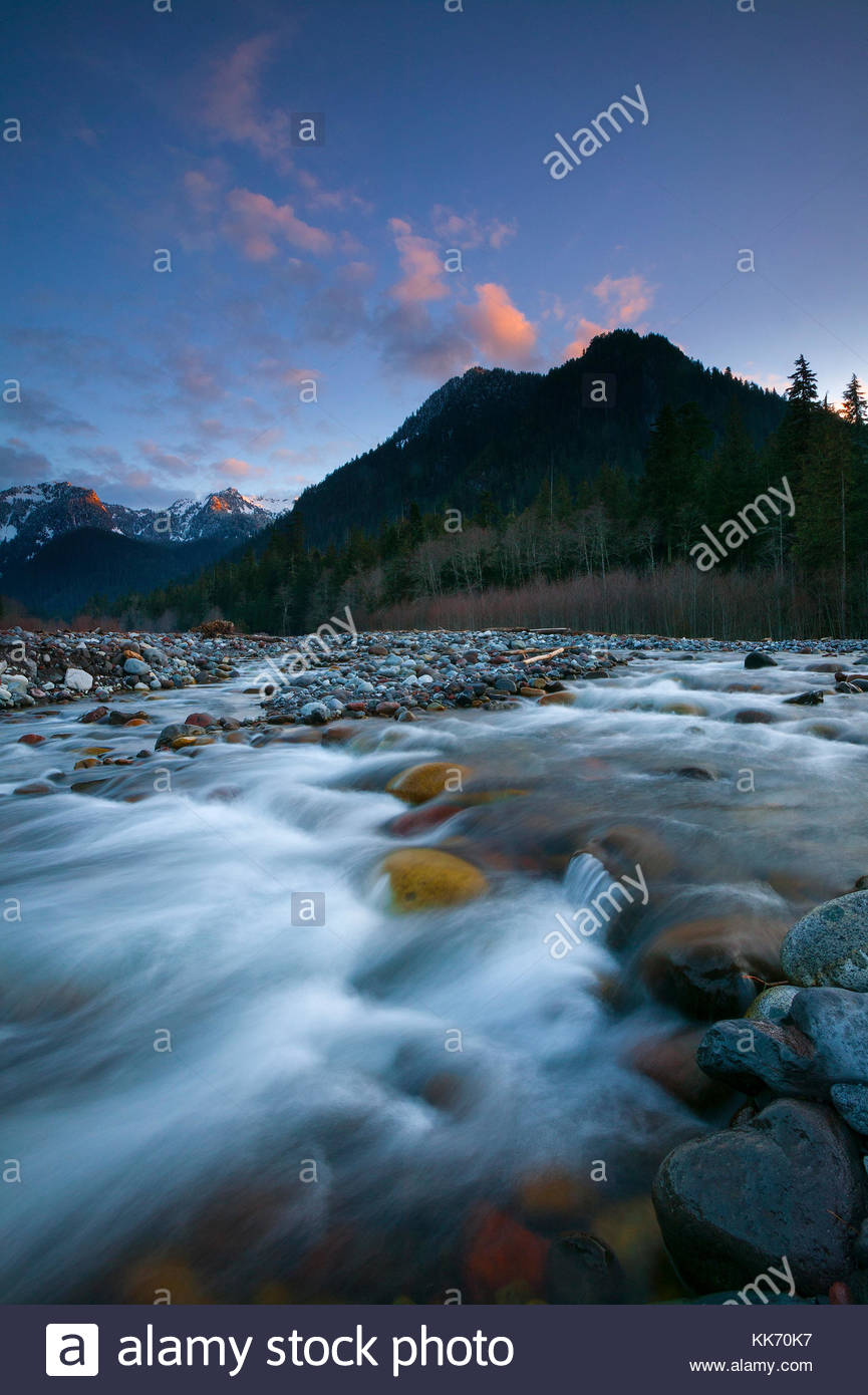 The Carbon River cascades over volcanic rocks left by Mount Rainier's most recent eruption. A dramatic sunset - Stock Image