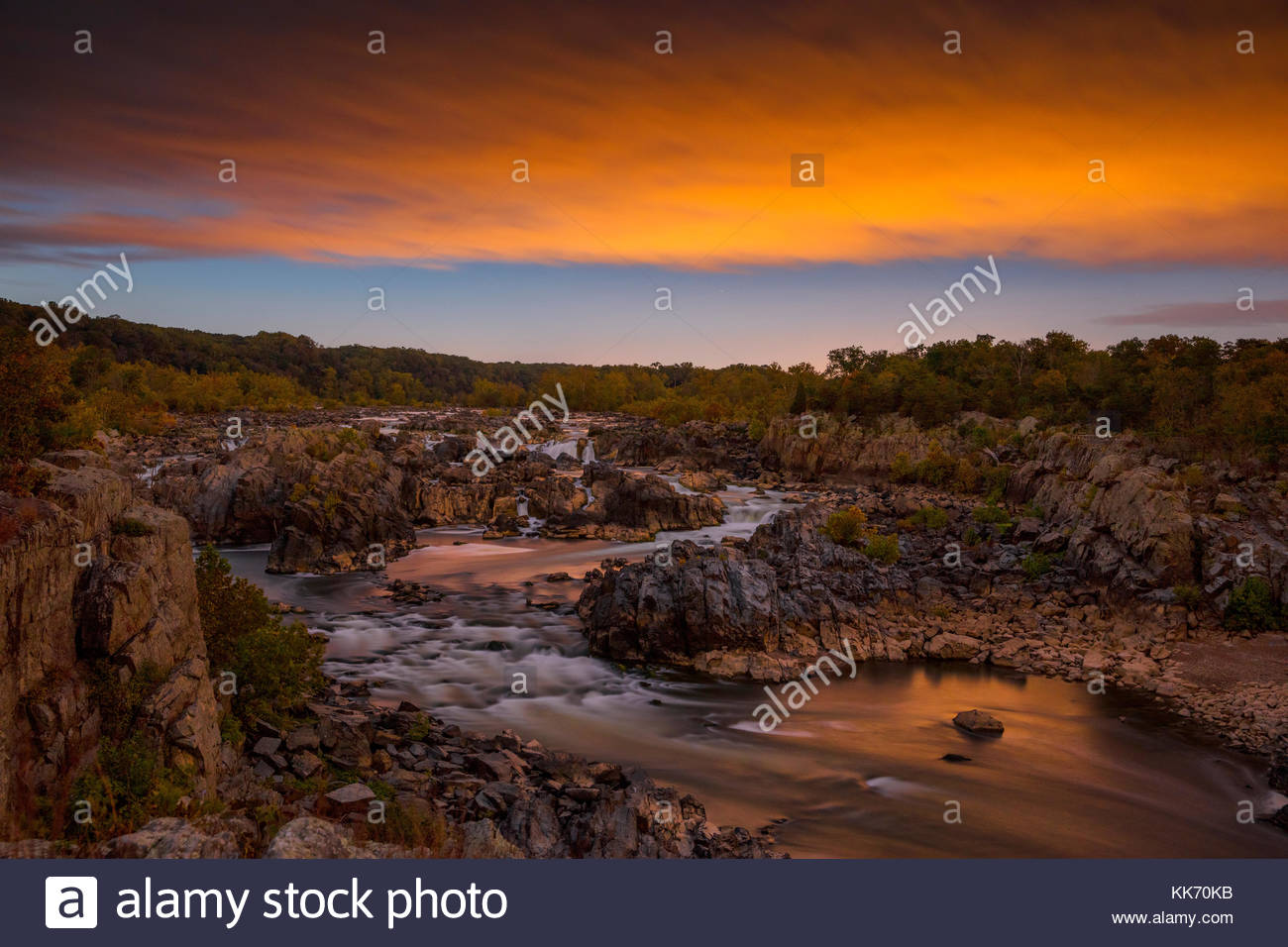 A fiery sunset colors the sky over the Great Falls of the Potomac River, located in Great Falls Park, Virginia. - Stock Image