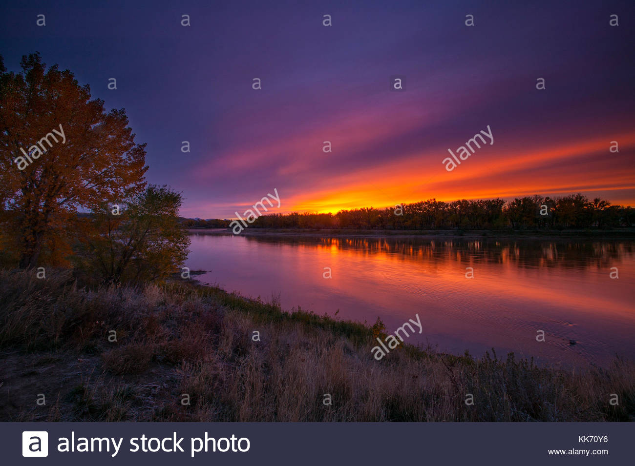 An autumn sunrise reddens the sky over the Missouri River at Coal Banks Landing in the Upper Missouri River Breaks - Stock Image
