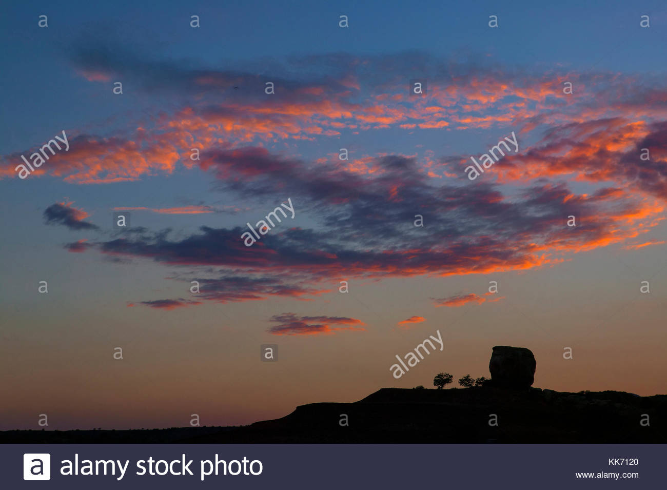 A layer of altocumulus clouds are turned fiery red by the setting sun as a large rock formation appears to observe - Stock Image