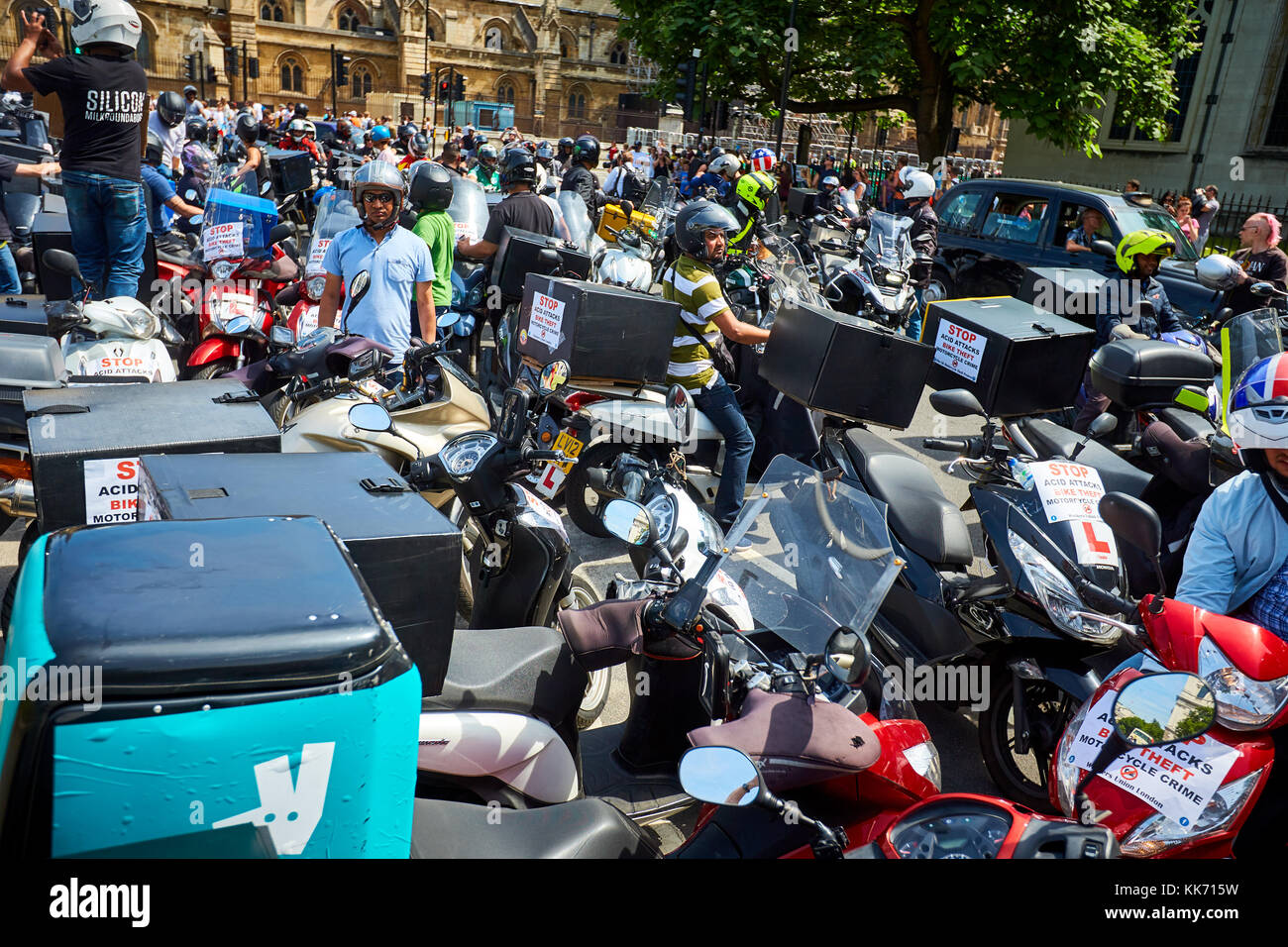 Moped riders, including couriers and delivery drivers, protest inParliament Square in London against a recent spate - Stock Image