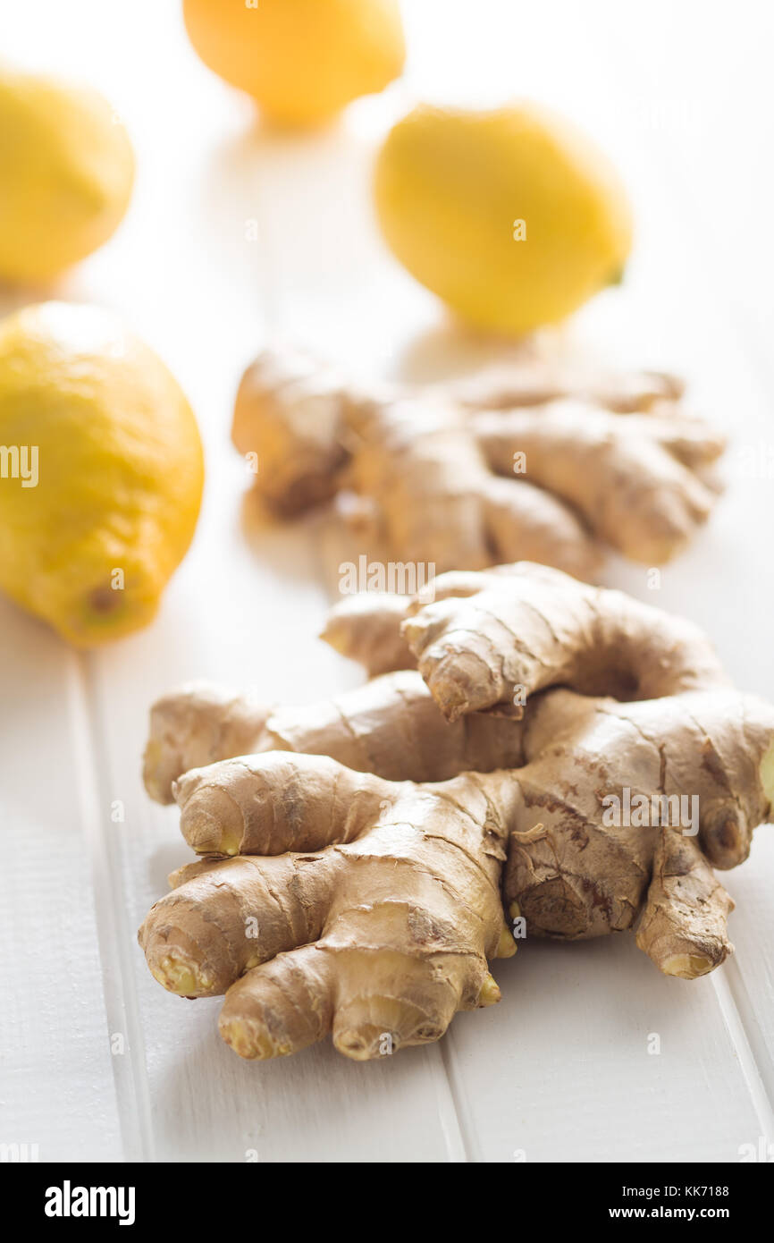 Ginger root and lemons on white table. - Stock Image