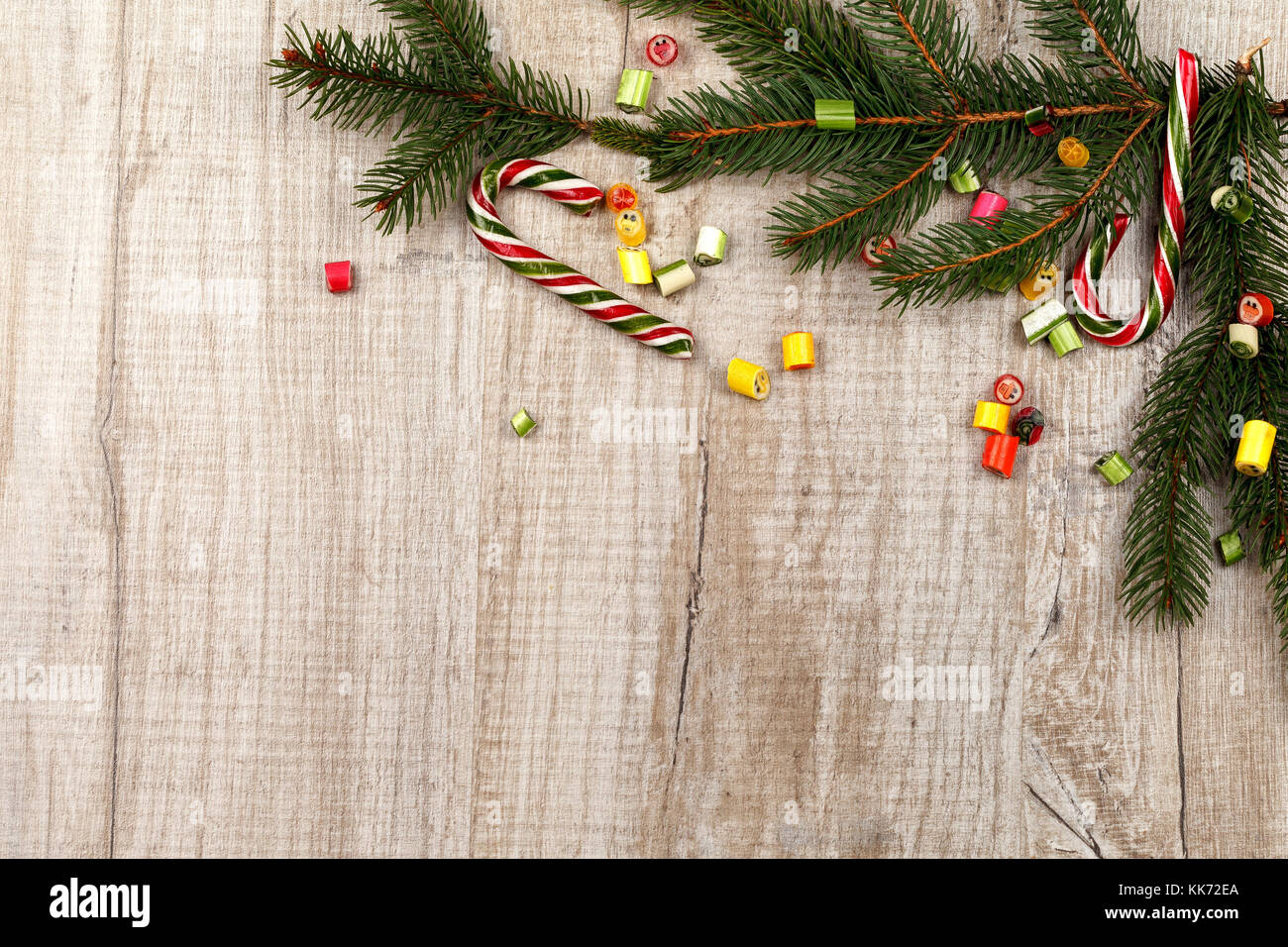 Christmas composition of fir branches, caramel sweets and caramel cane. On a light wooden background. Stock Photo