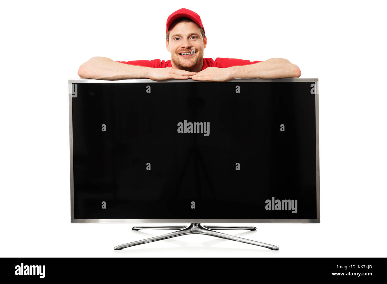 smiling salesman in red uniform over big blank tv screen isolated on white background - Stock Image