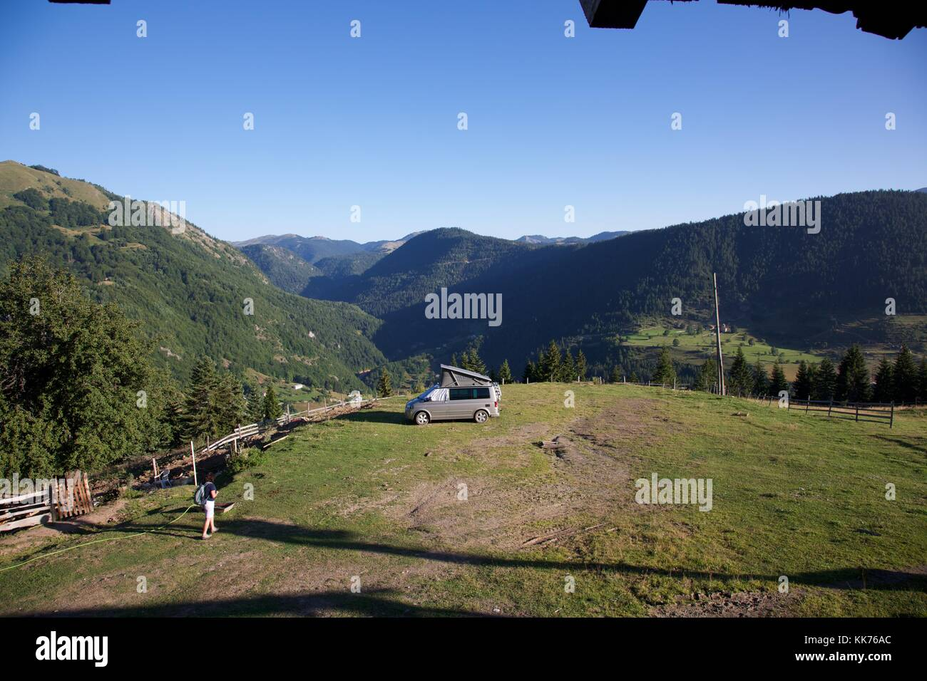 A female camper returning to her motorhome in a field high on a hill above the Rugova Valley Kosovo on a bright Stock Photo