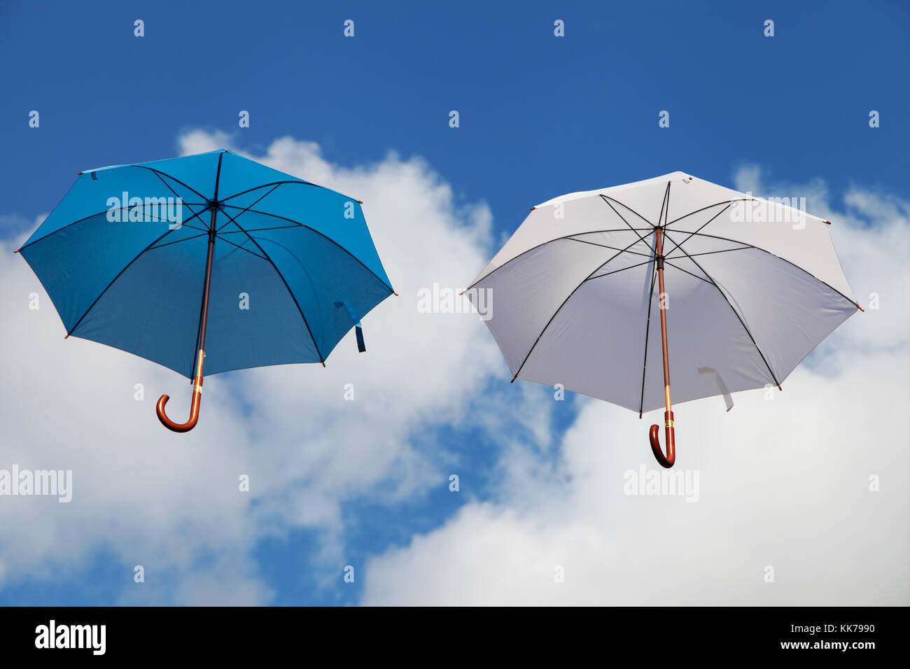Two Floating Umbrellas in Blue and White - Stock Image