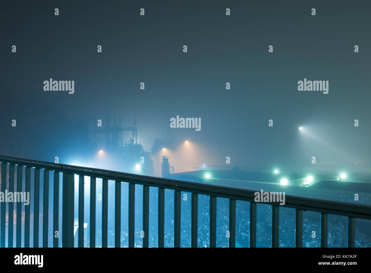Railing in Front of an Industrial Area during Night - Stock Image
