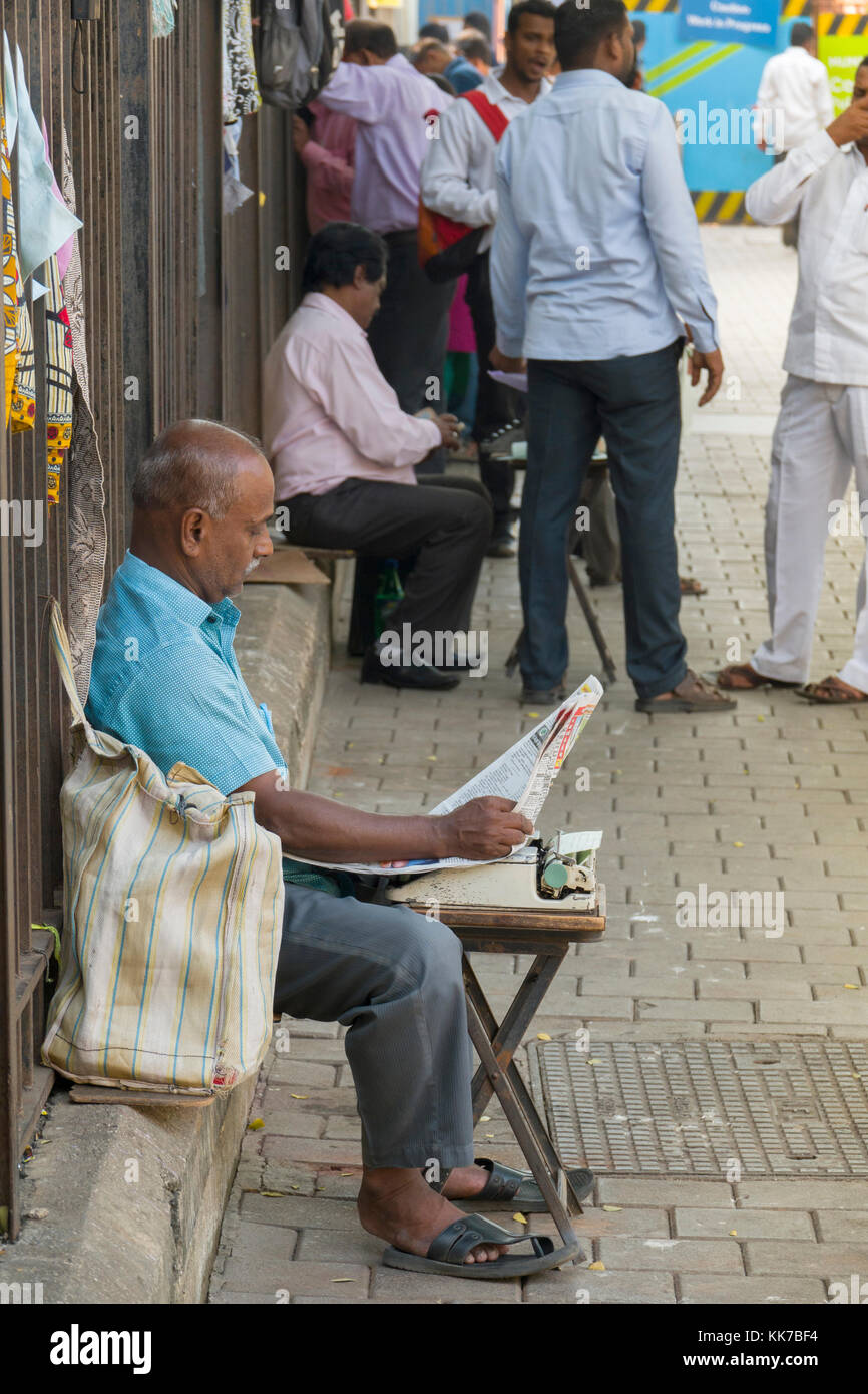 Legal document typist reading newspaper in street outside Bombay High Court in Mumbai, India - Stock Image