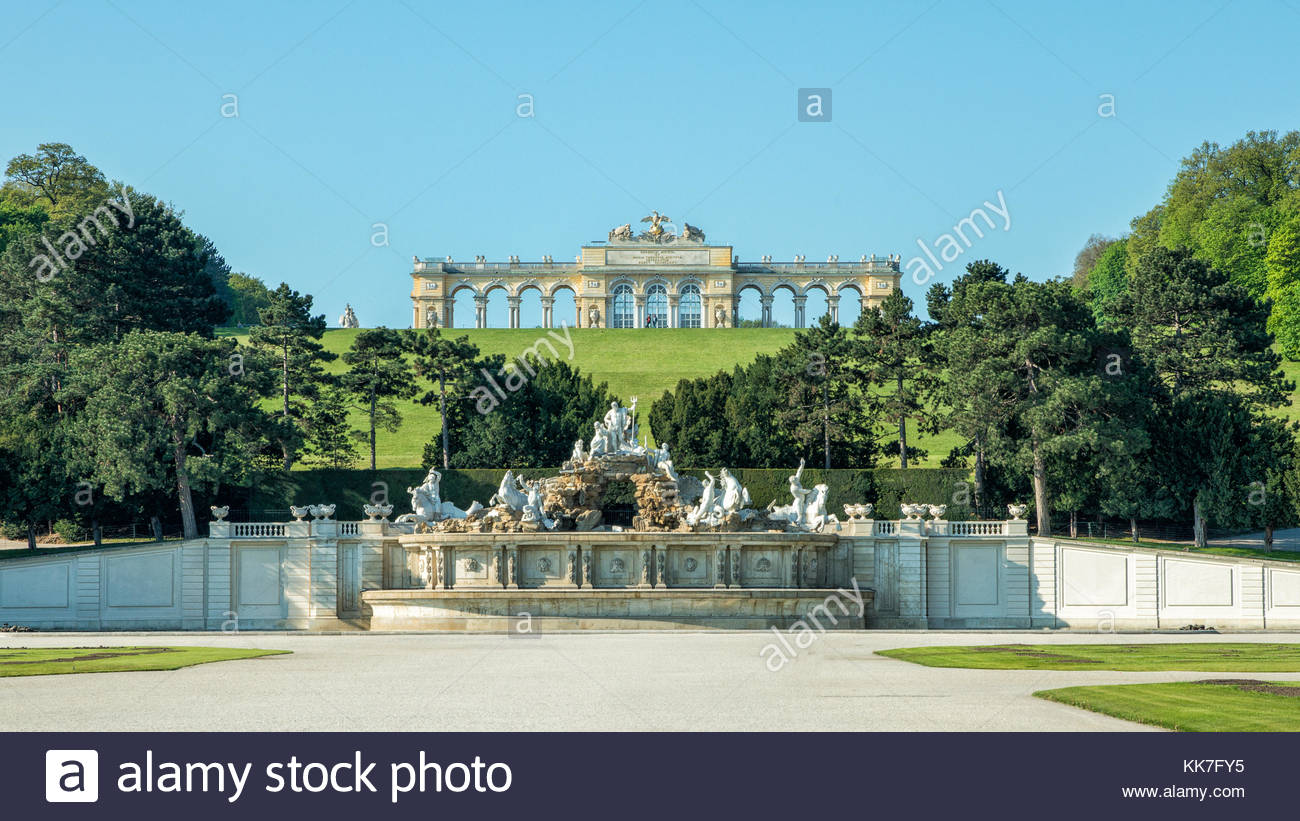 Neptune Fountain, Great Parterre and Gloriette under a blue sky - at Schönbrunn Palace, Vienna - Stock Image