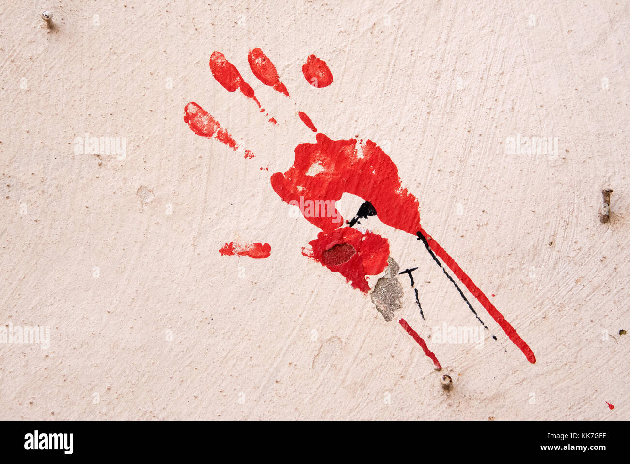 Hand print in red paint on a white wall - Stock Image