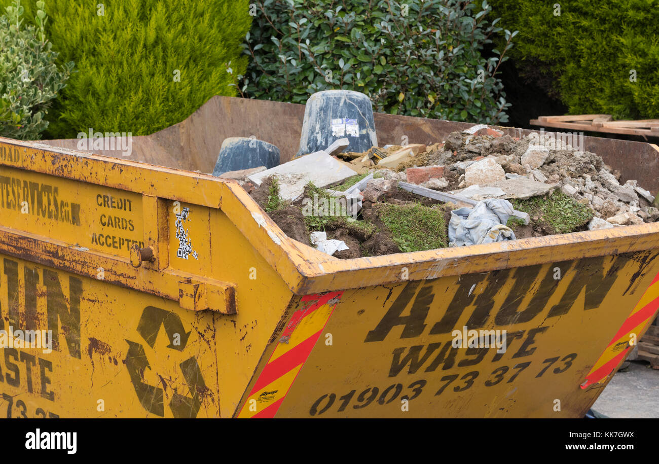 A skip full of rubble and building waste on a private construction site in the UK. - Stock Image