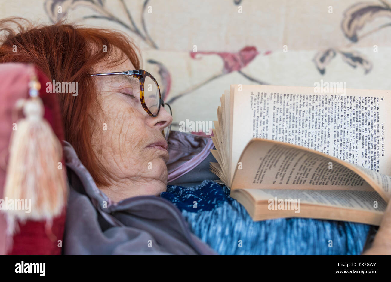 Elderly woman fallen asleep while laying on a sofa reading a book. - Stock Image
