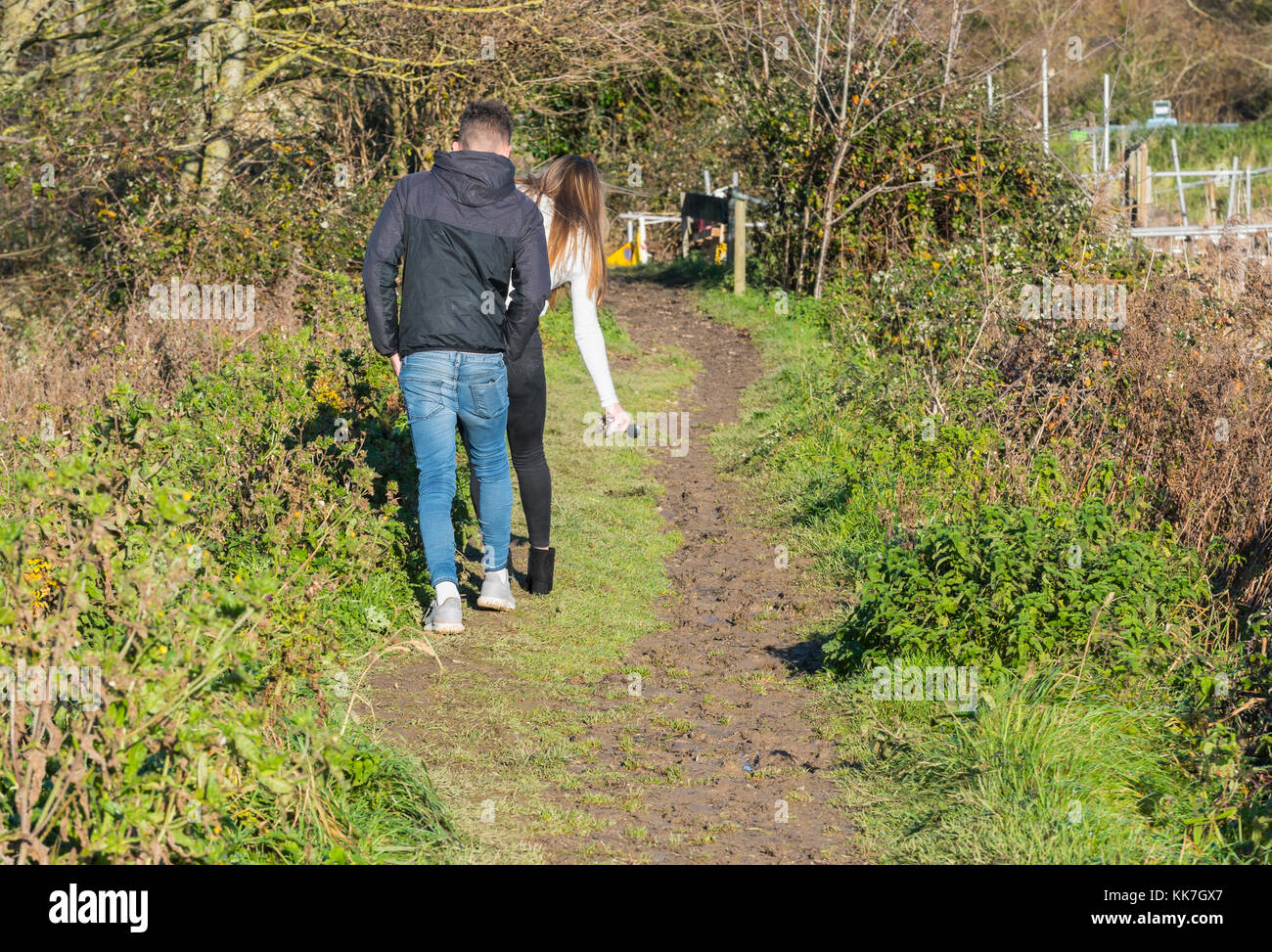 Young couple walking along a muddy towpath trying to avoid the mud. - Stock Image