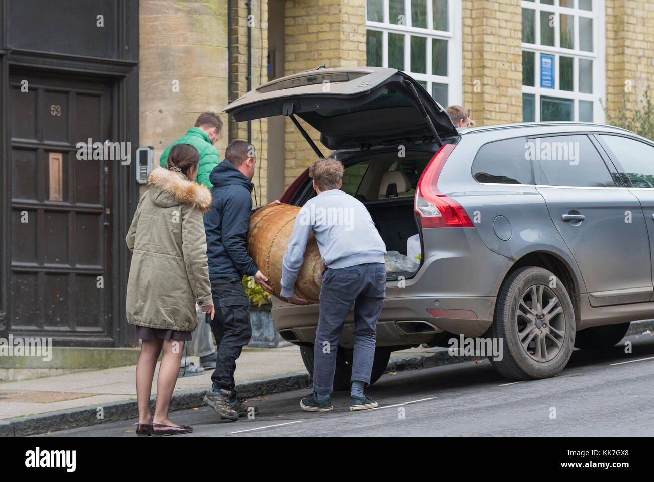 People loading heavy items into a car. - Stock Image