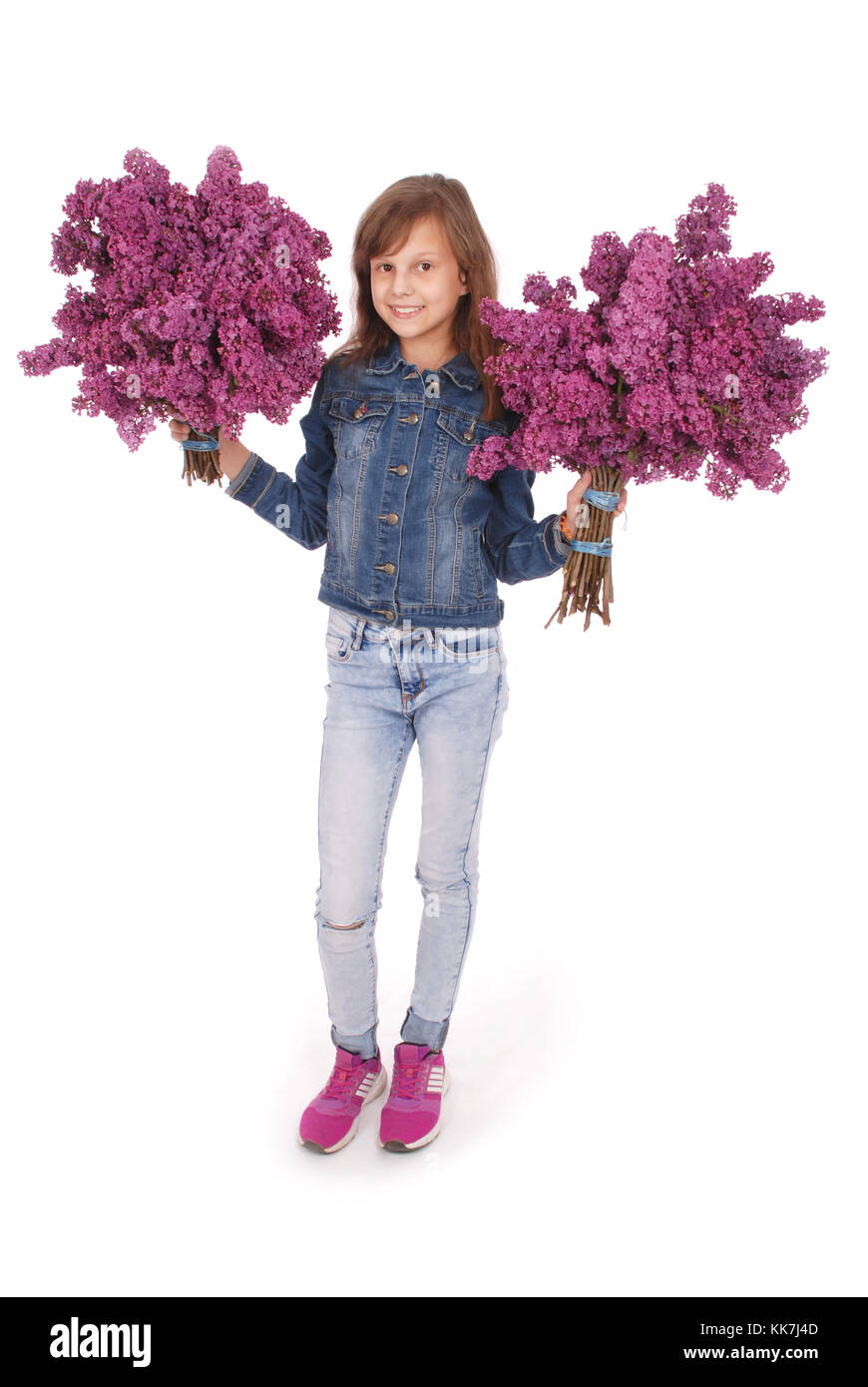 Teenage girl standing with lilac in both hands. Isolated on white background - Stock Image