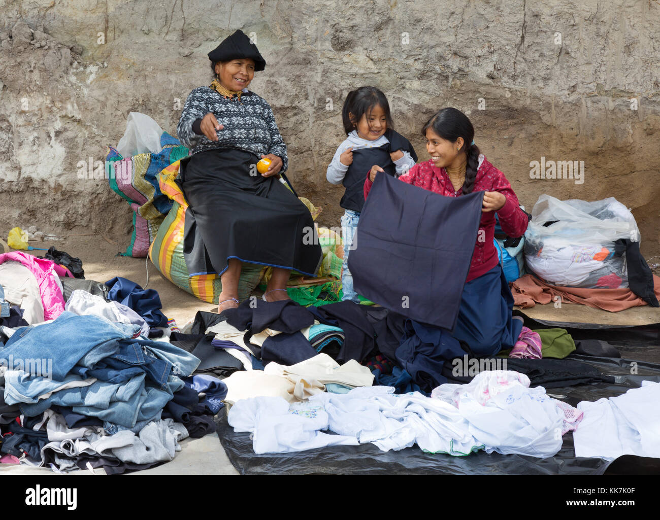 Three generations of women from the same family selling clothes on a stall, Otavalo market, Otavalo, Ecuador, South - Stock Image