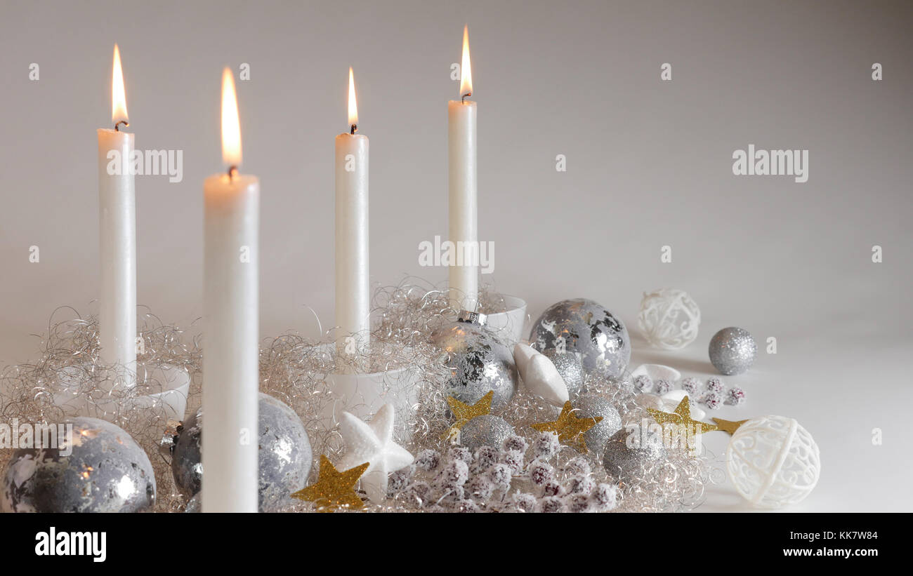 festive christmas decoration with four candlelights glitter balls and sparcling angel hair close up shot on white background with copy space