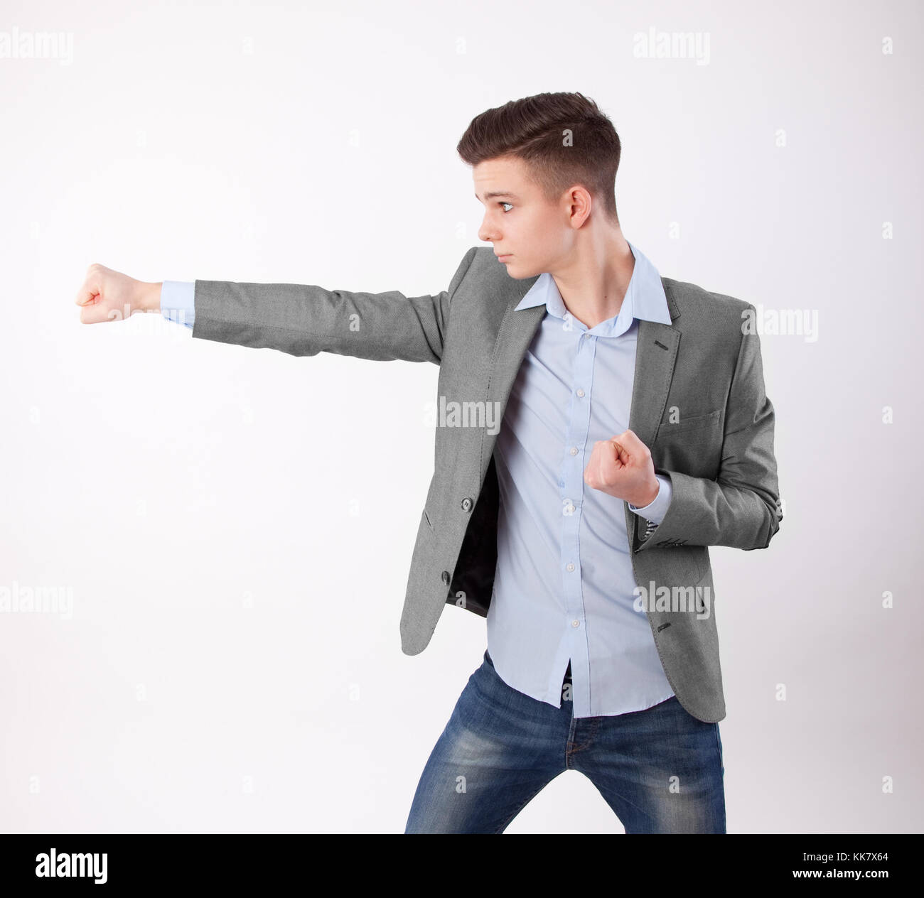young businessman does a karate punch - Stock Image