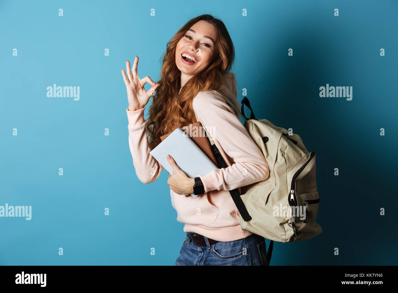 d0dae1b2ae Portrait of a happy friendly girl student with backpack holding books and  showing ok gesture isolated over blue background