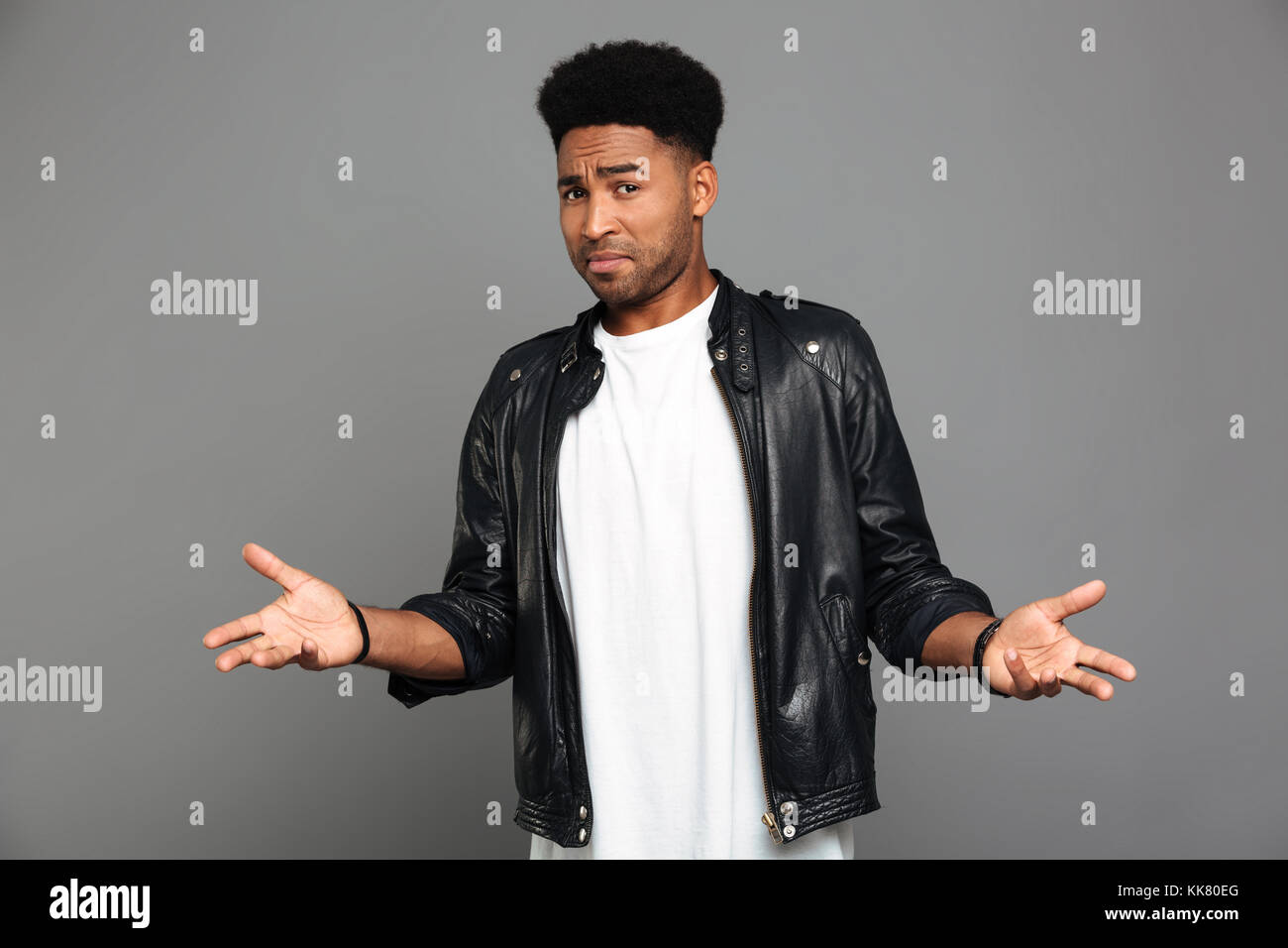 Close-up  photo of amazed afro american man in leather jacket, looking at camera, isolated over gray background - Stock Image