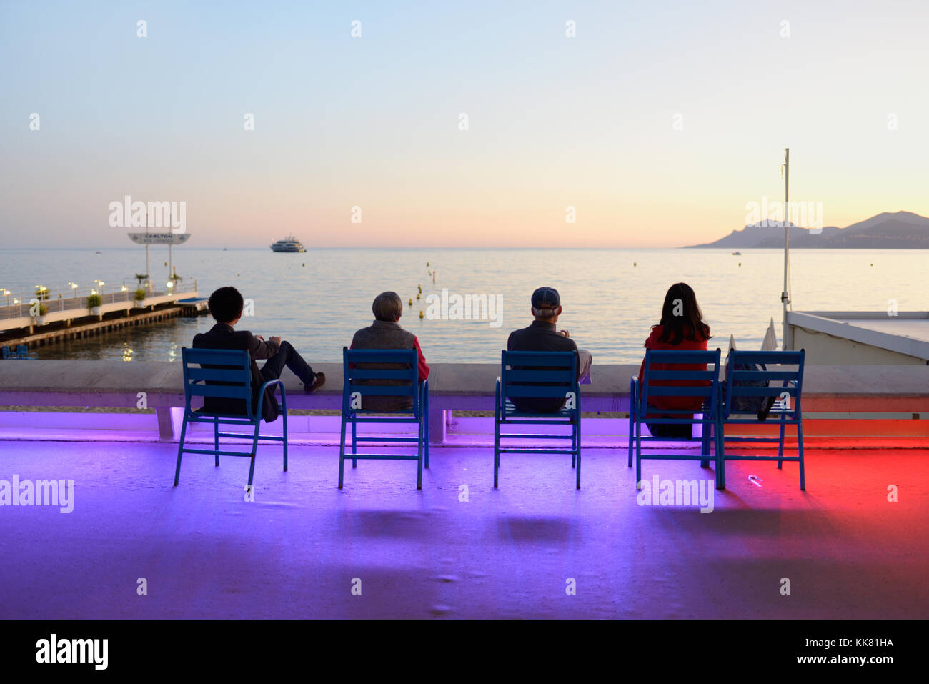 Four Tourists Enjoy the Sunset on the Boulevard de la Croisette, Cannes, at Dusk, with Dramatic Colour Street Lighting, French Riviera, france Stock Photo