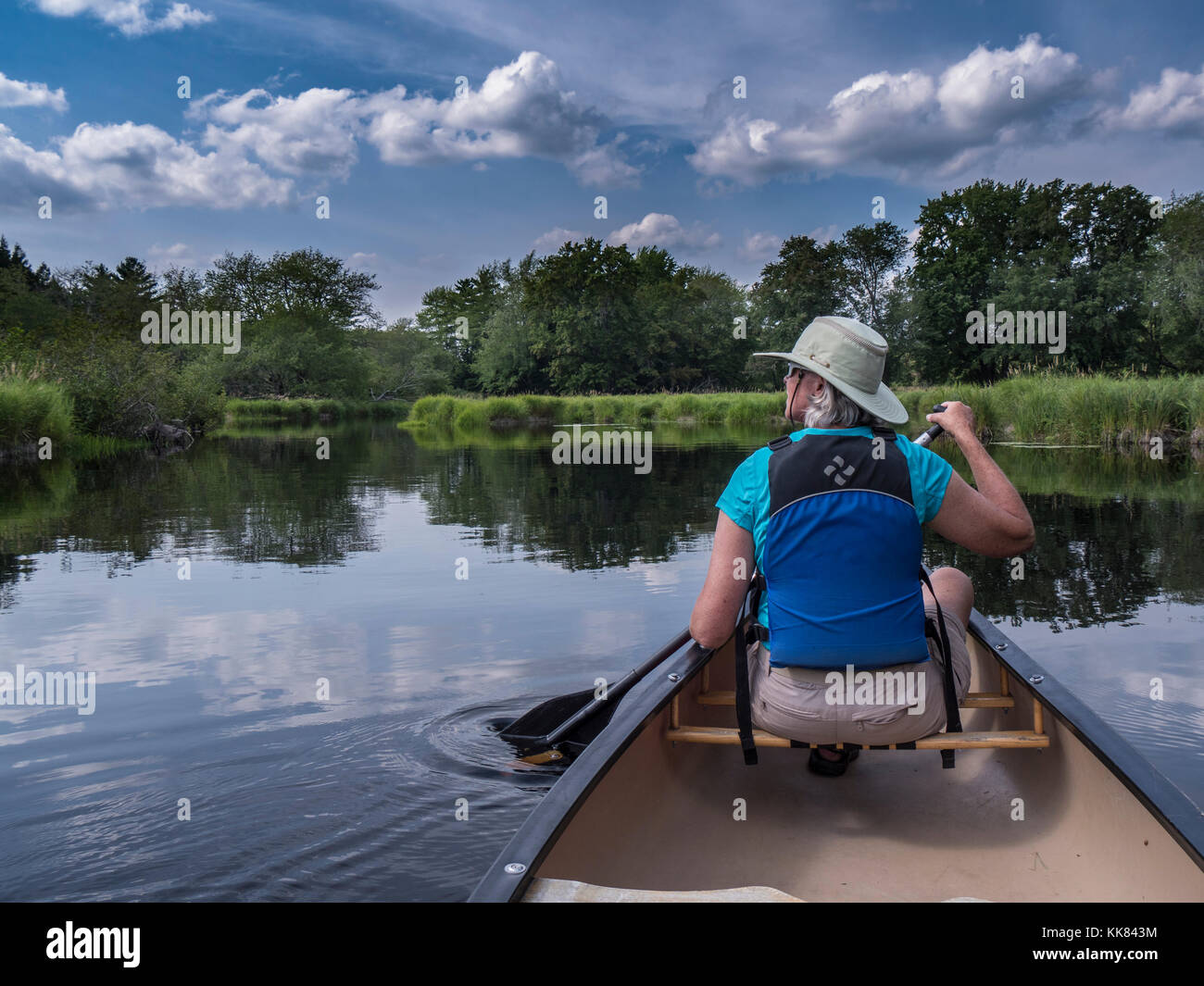 Woman paddles the Mersey River, Kejimkujik National Park, Nova Scotia, Canada. - Stock Image