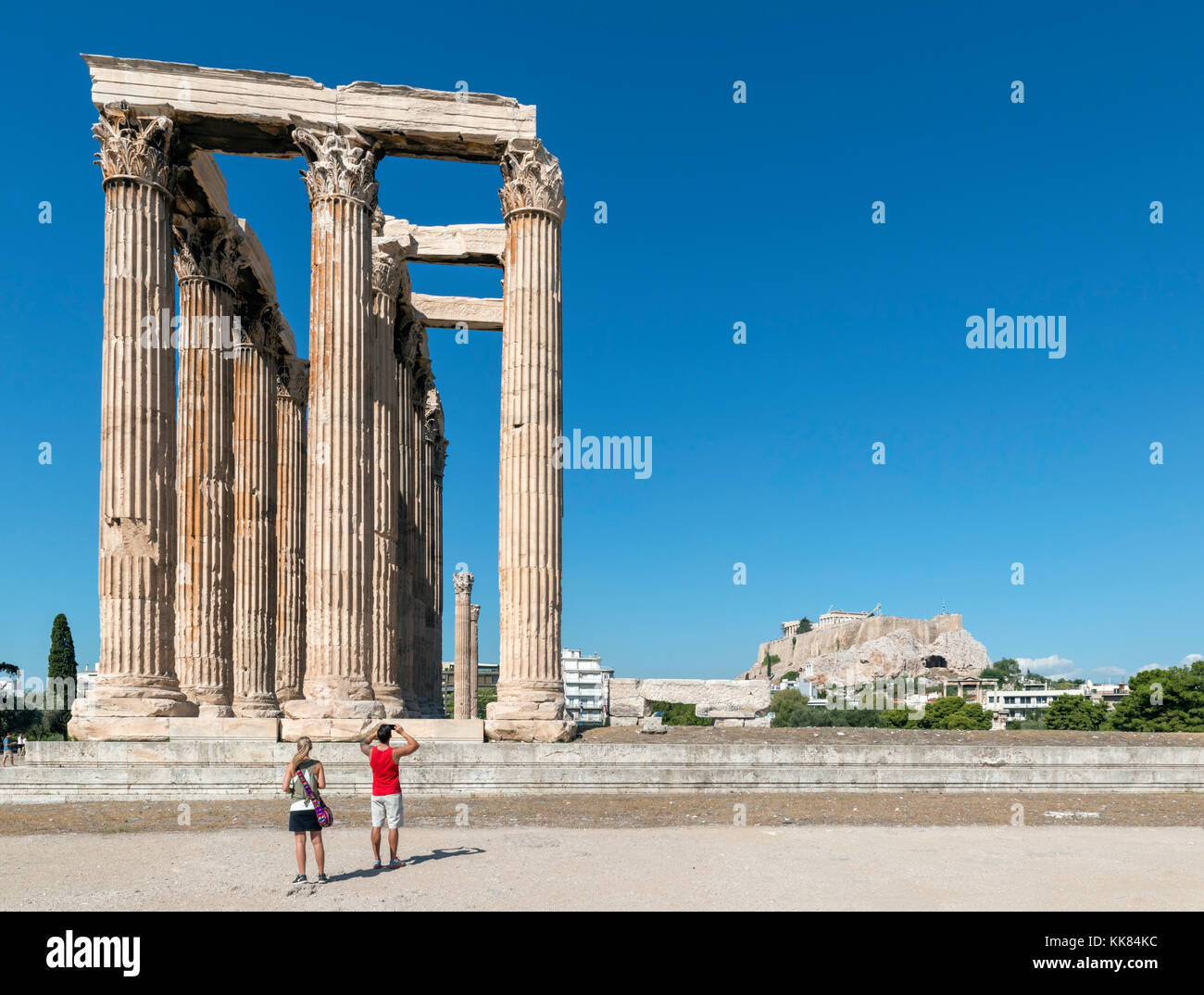 Couple in front of the Temple of Olympian Zeus (Olympeion) with the Acropolis in the background, Athens, Greece - Stock Image