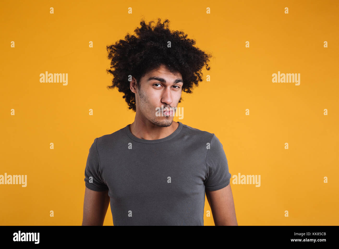 Portrait of a funny young afro american man looking at camera and grimacing isolated over orange background - Stock Image