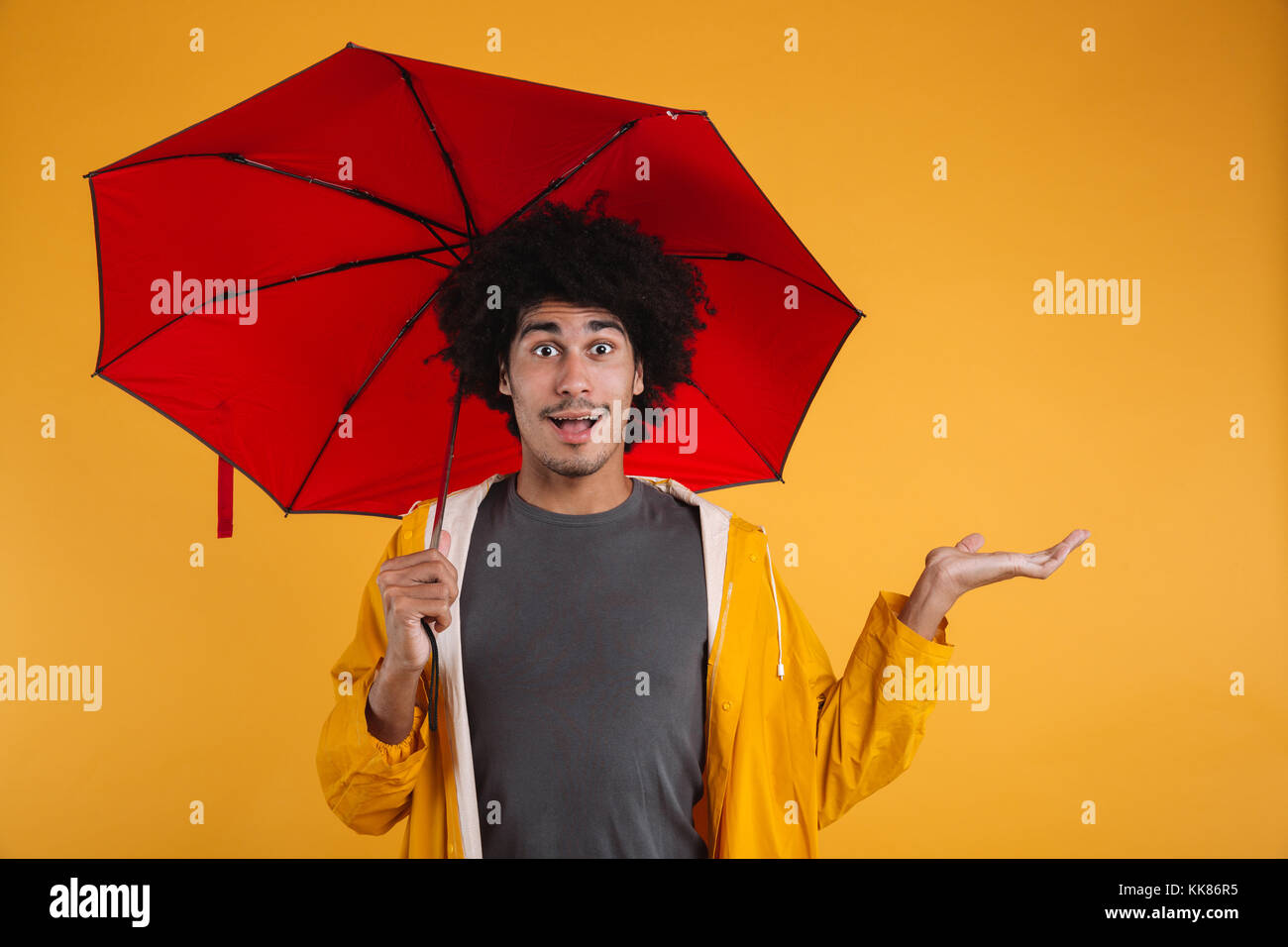 Portrait of an excited afro american man dressed in raincoat holding umbrella while standing with outstretched hand Stock Photo