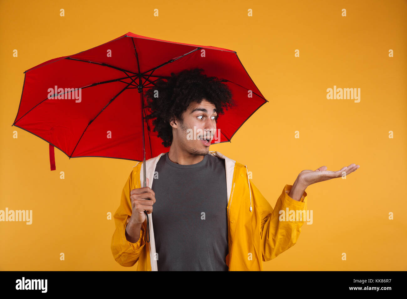 Portrait of a happy afro american man dressed in raincoat holding umbrella while standing with outstretched hand Stock Photo