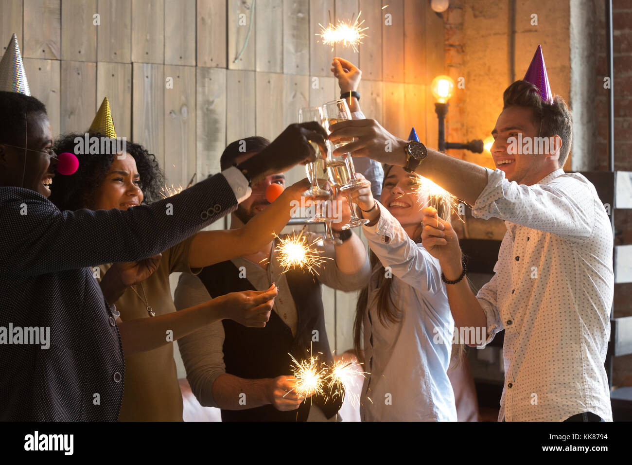 Multi-ethnic young people celebrating New year clinking glasses  - Stock Image