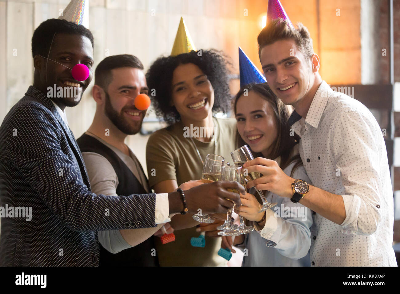 Diverse friends clinking champagne glasses looking at camera cel - Stock Image
